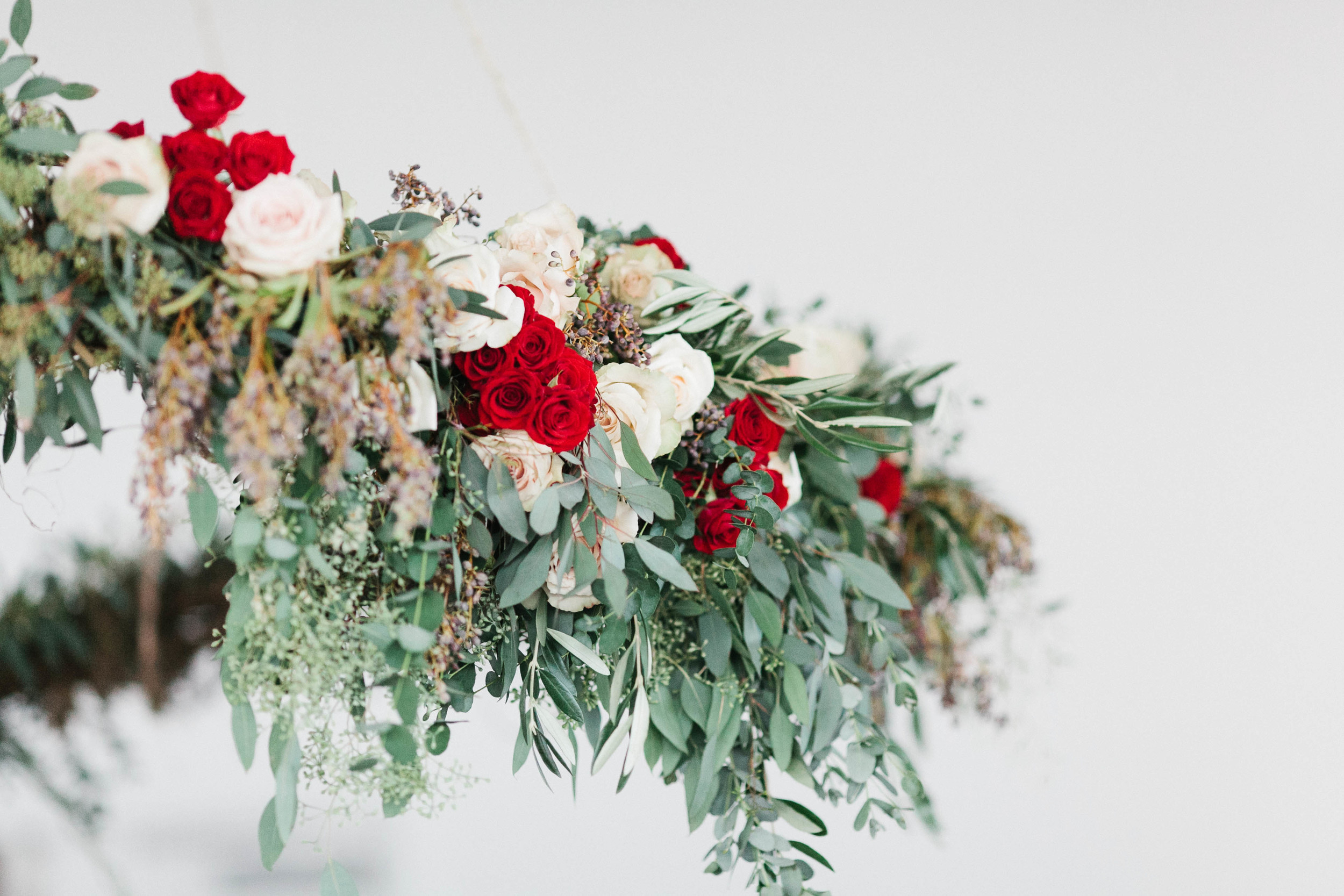 Suspended floral ceremony backdrop with deep red accents