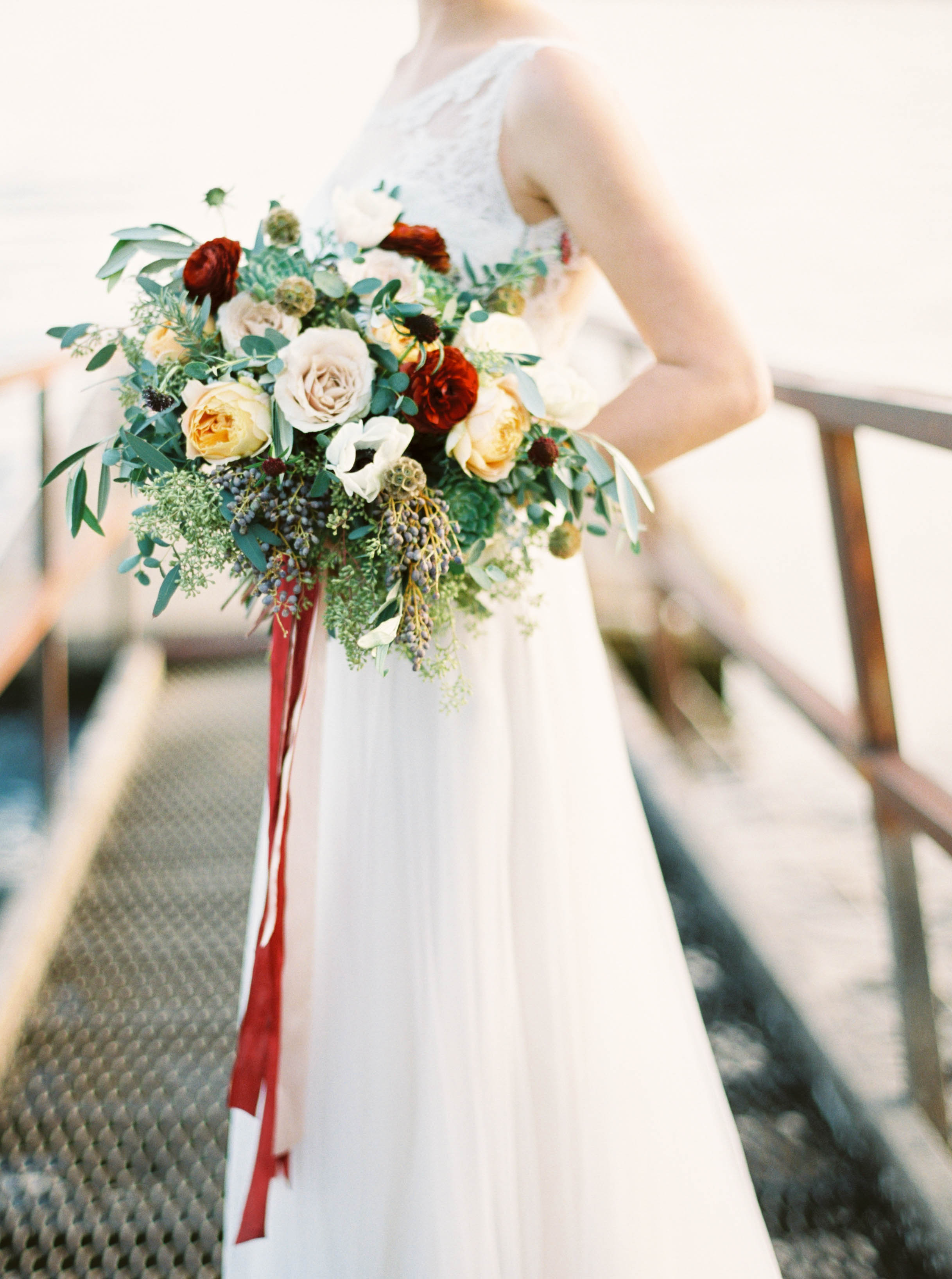 Loose, trailing bouquet with garden roses, ranunculus, and olive branches // Destination Floral Design