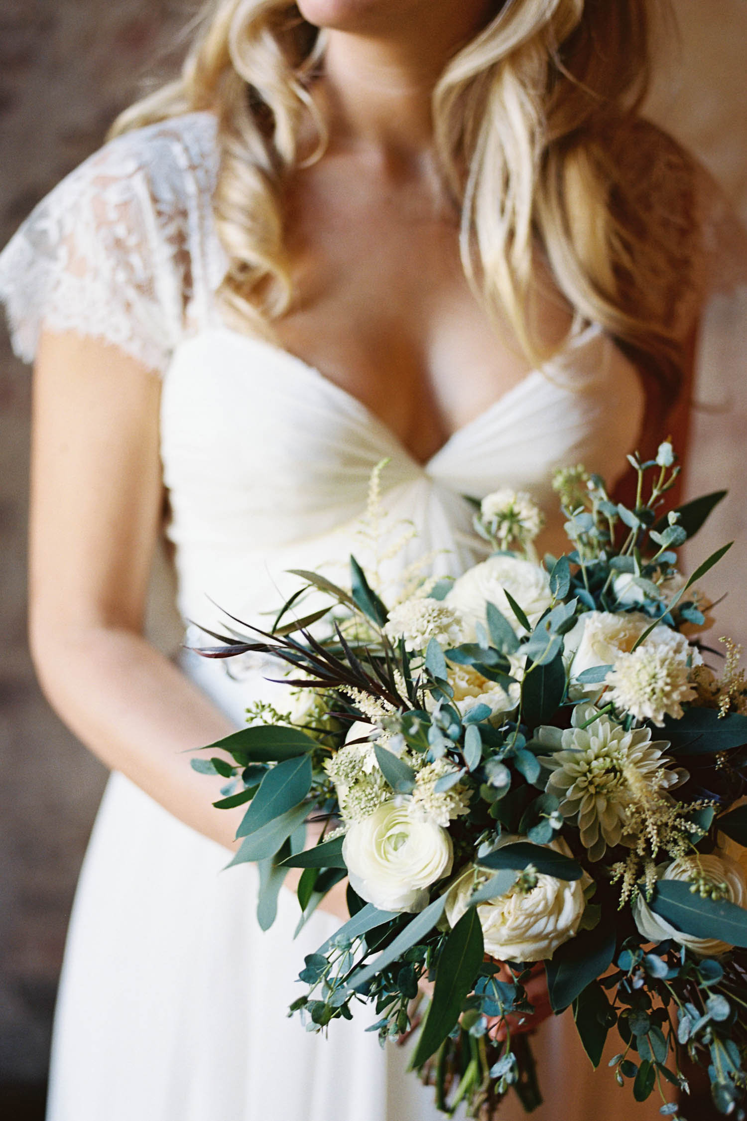 Loose, natural bridal bouquet of greenery and ivory flowers