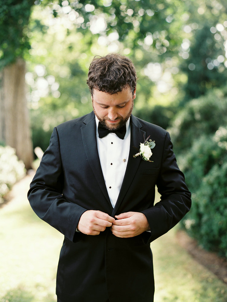 Groom in tux with white and greenery boutonniere // Nashville Floral Design