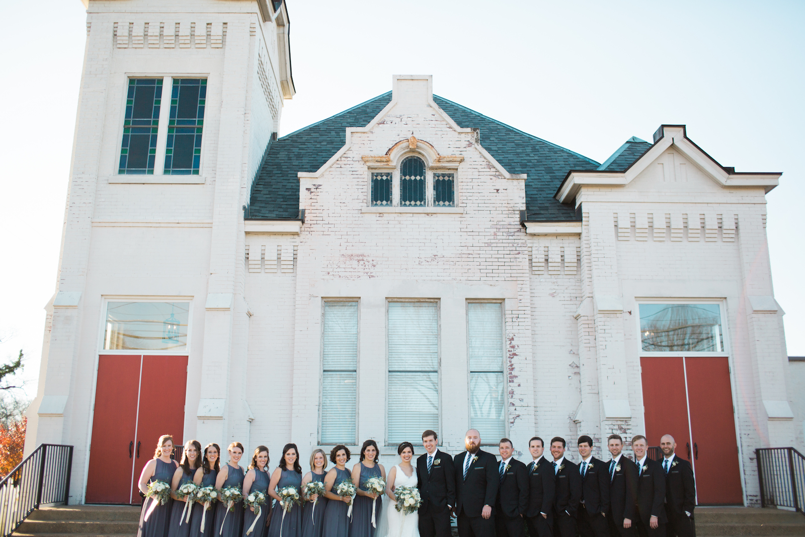 Bridal party in front of little white church with red doors // Southern Wedding Florist