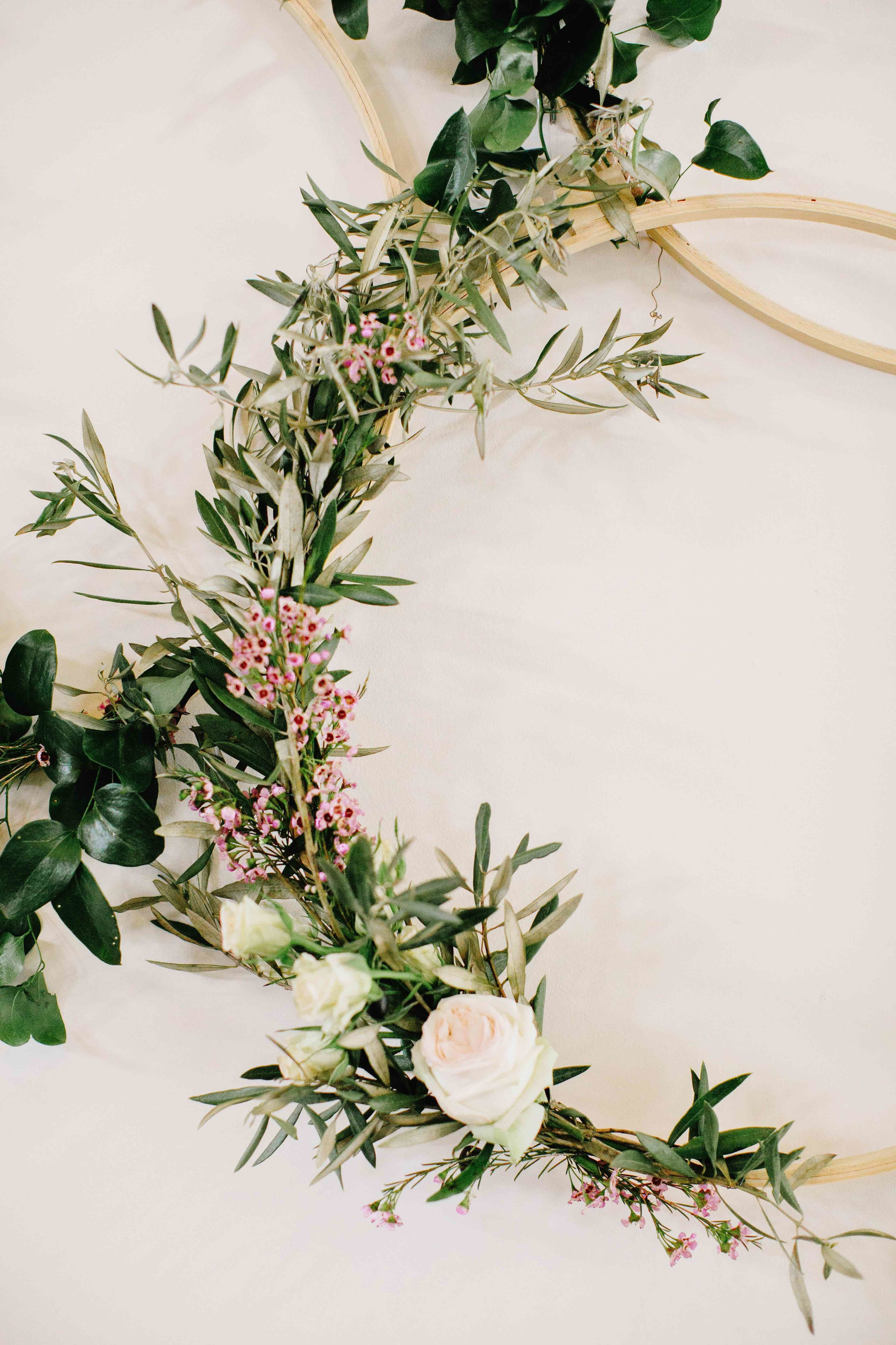 Detail shot of floral installation with wooden hoops on a white wall // Nashville Wedding Florist