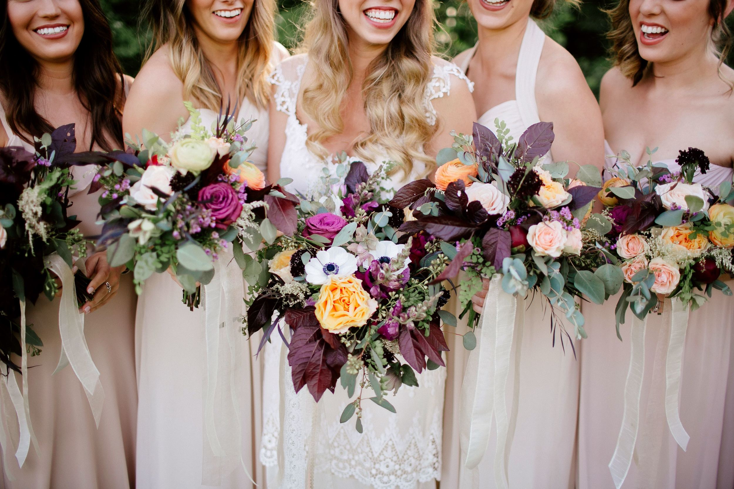 Bohemian bridal party with florals in lavender, peach, and maroon