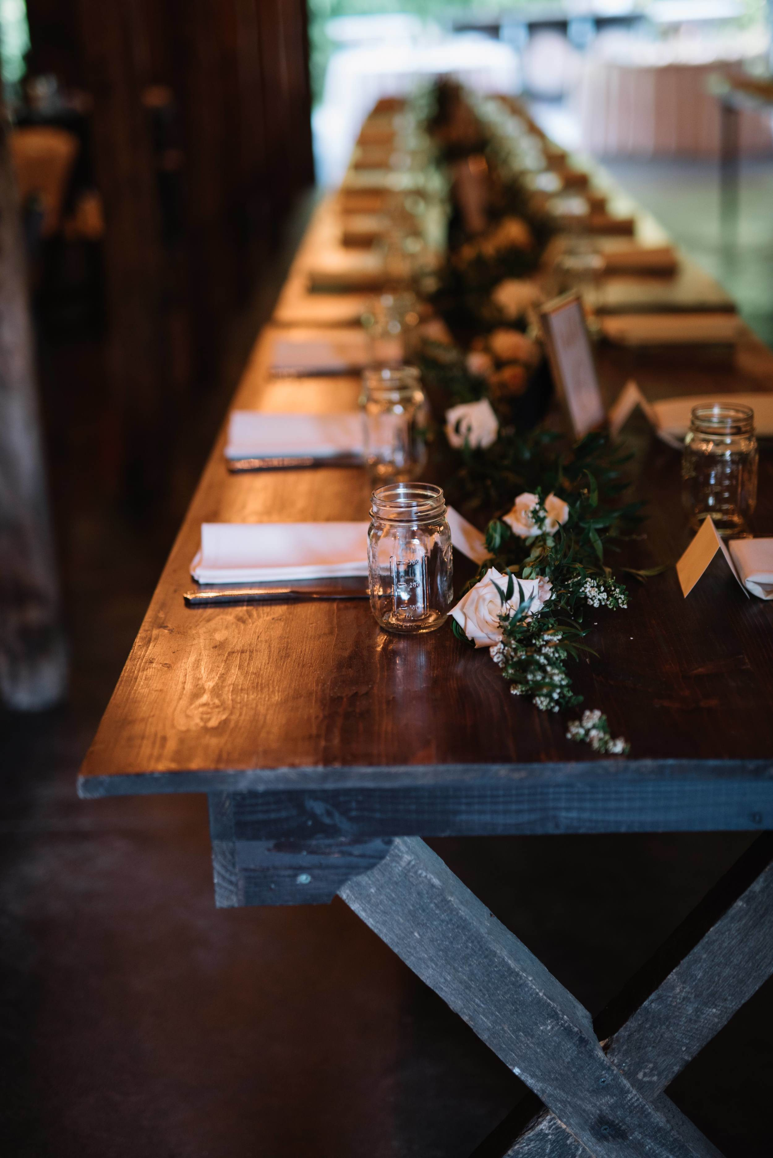 Lush greenery garland on farm tables with floral accents // Nashville Wedding Florist