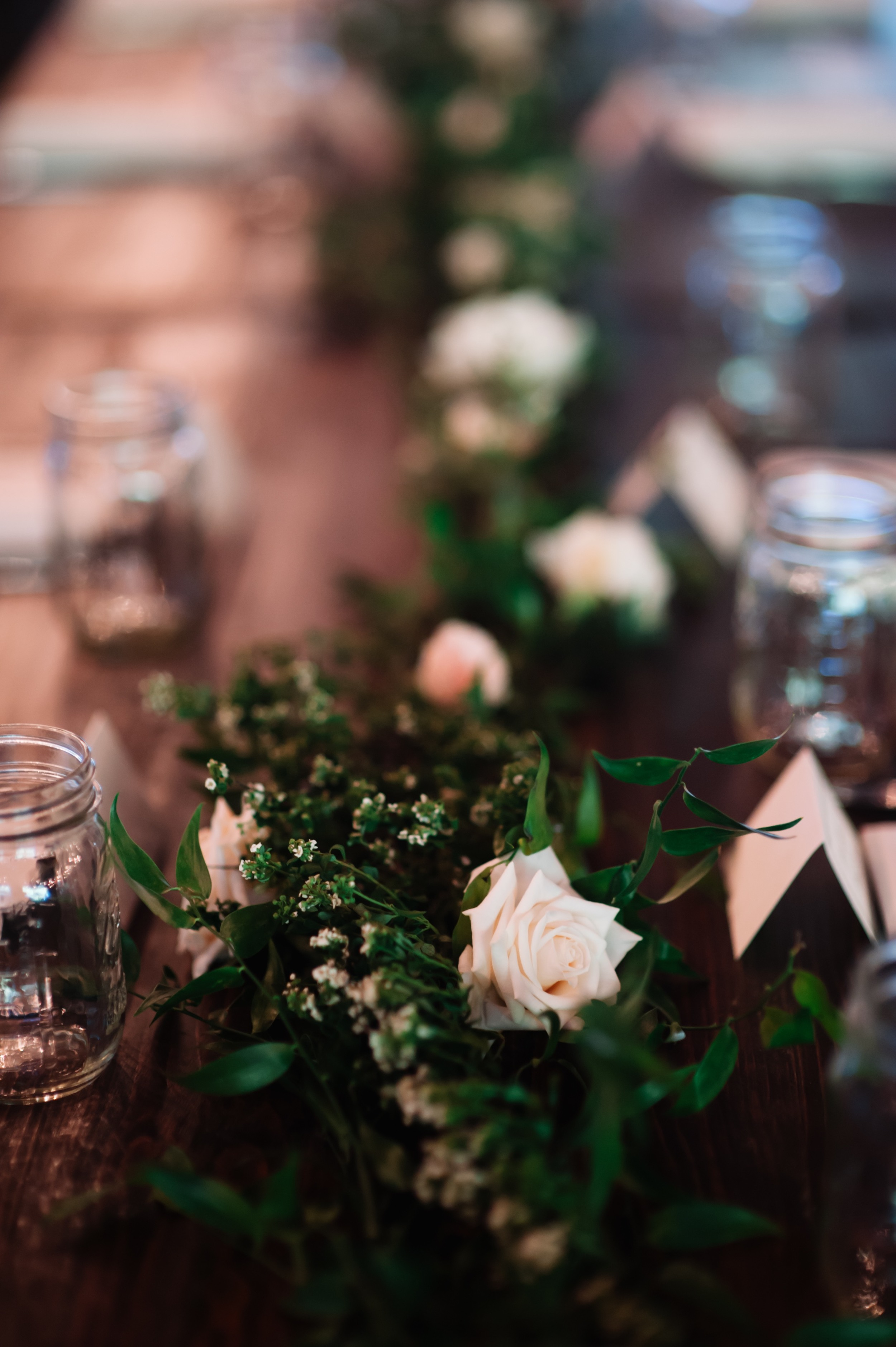 Blush, ivory, and greenery floral garlands on farm tables // Nashville Barn Wedding