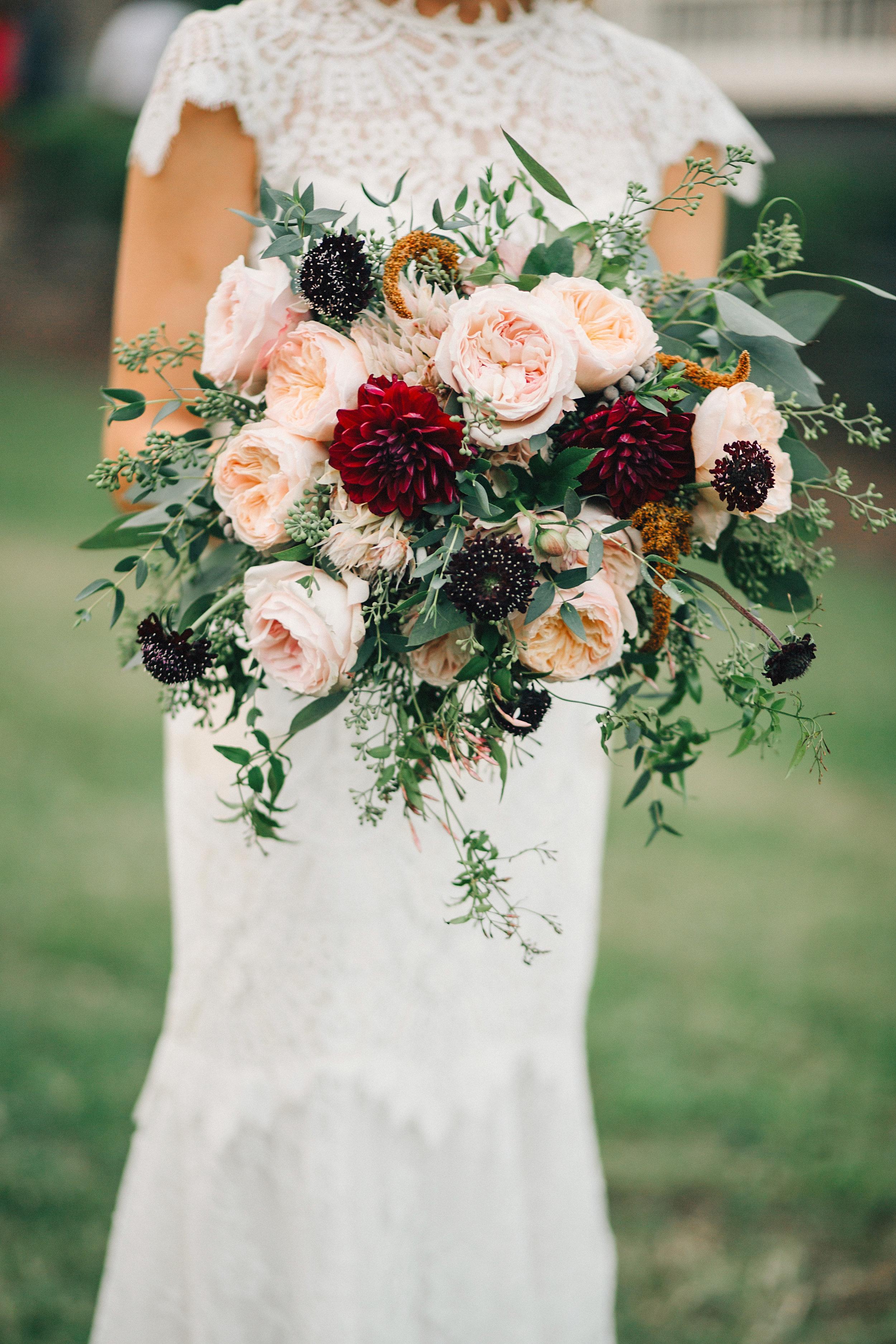 Lush, organic bridal bouquet with burgundy dahlias, peach garden roses, and trailing greenery // Nashville Wedding Floral Design