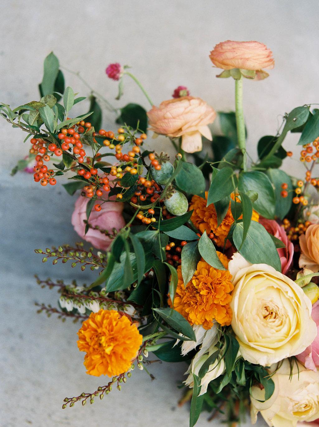 Bright, summery bridal bouquet with rosy pink garden roses, coral ranunculus, and orange marigolds // Nashville Wedding Florist