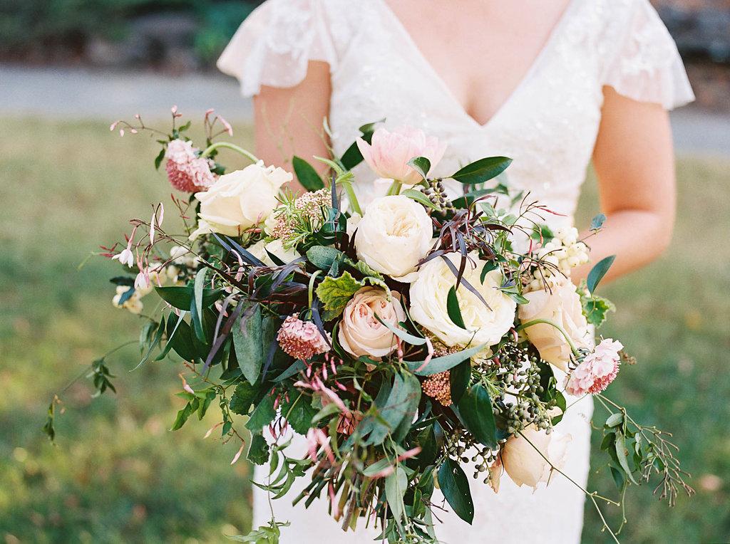 Lush, natural bridal bouquet with garden roses, tulips, blush ranunculus, and greenery in botanical garden // Nashville Wedding Floral Design