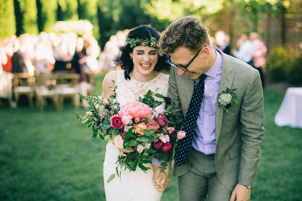 Joyful couple right after the wedding ceremony! Loose, untamed bridal bouquet with peonies, ranunculus, and tulips // Nashville Wedding Floral Designer