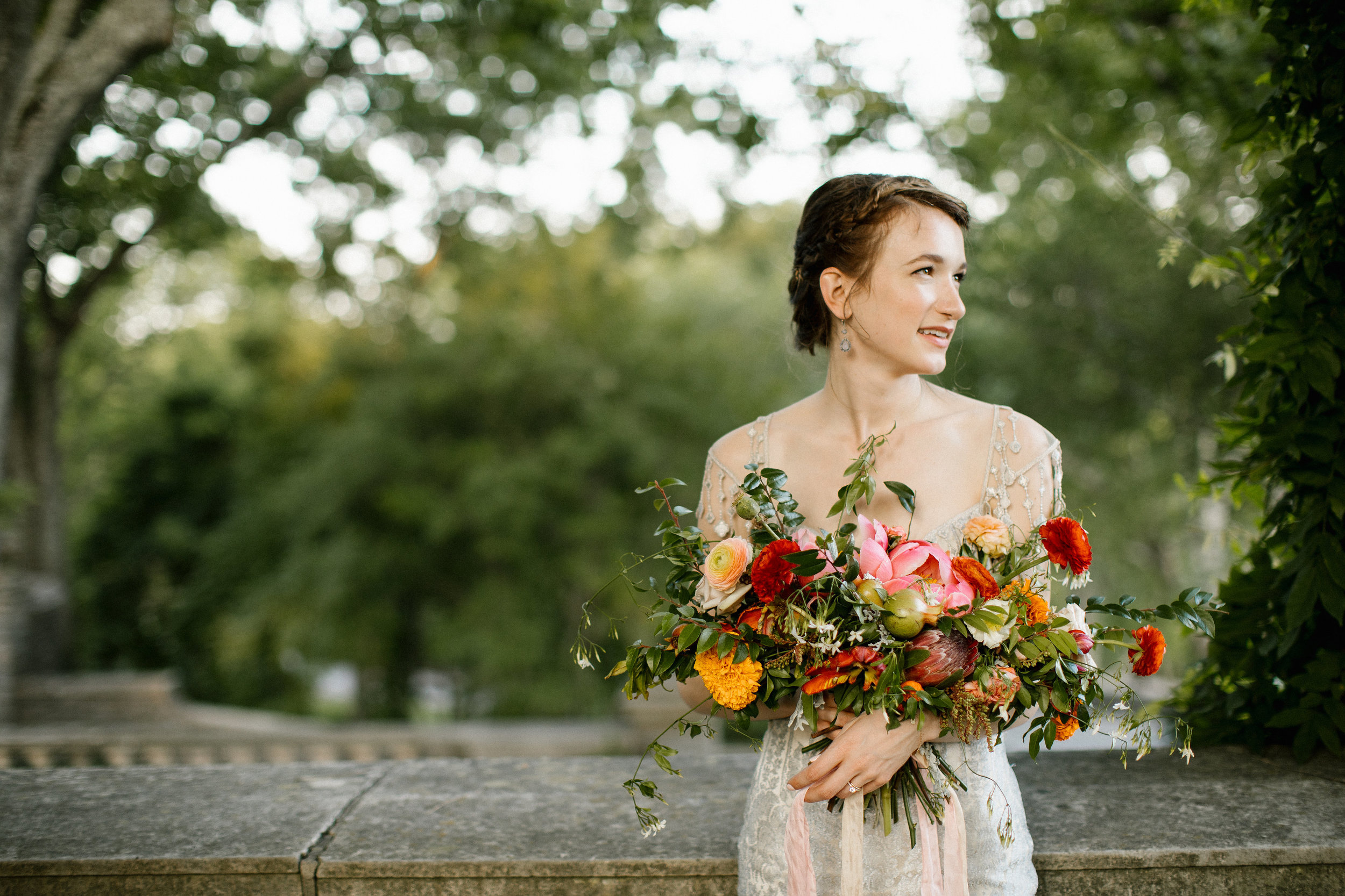 Red, coral, golden yellow, and orange bridal bouquet with lush, untamed greenery // Nashville Wedding Florist