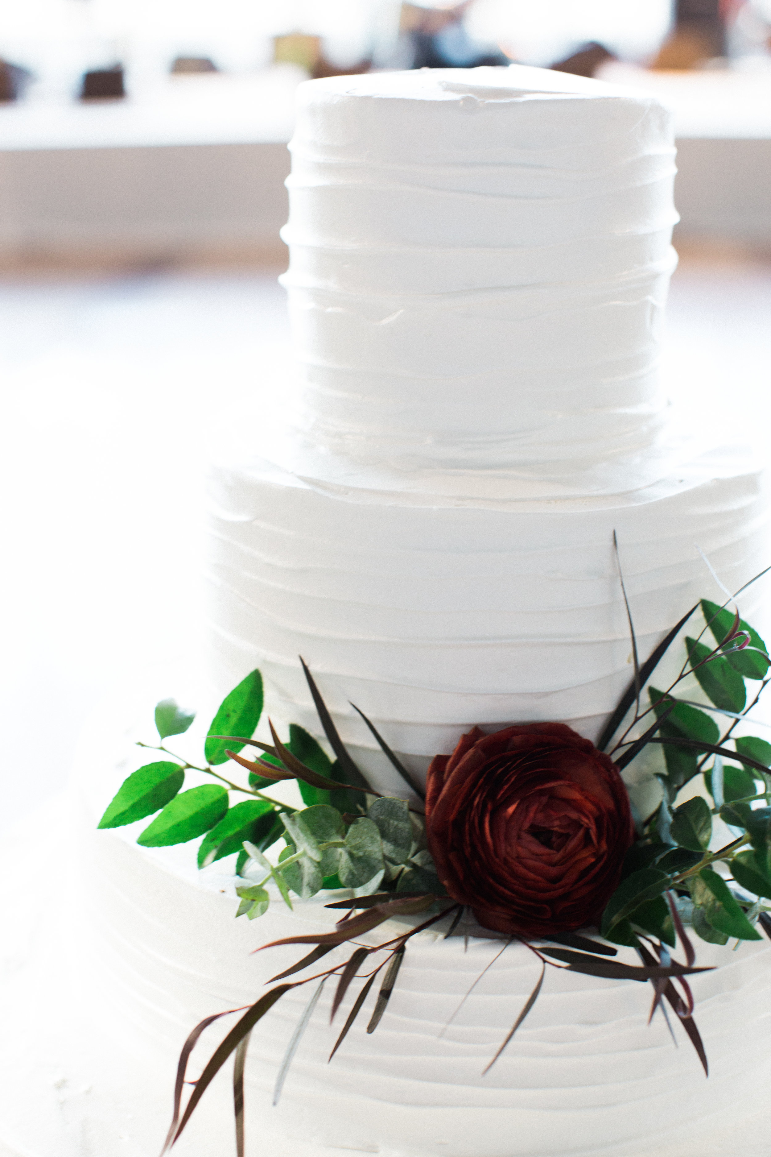 Classic white cake with a single burgundy ranunculus and touches of green // Nashville Wedding Florals