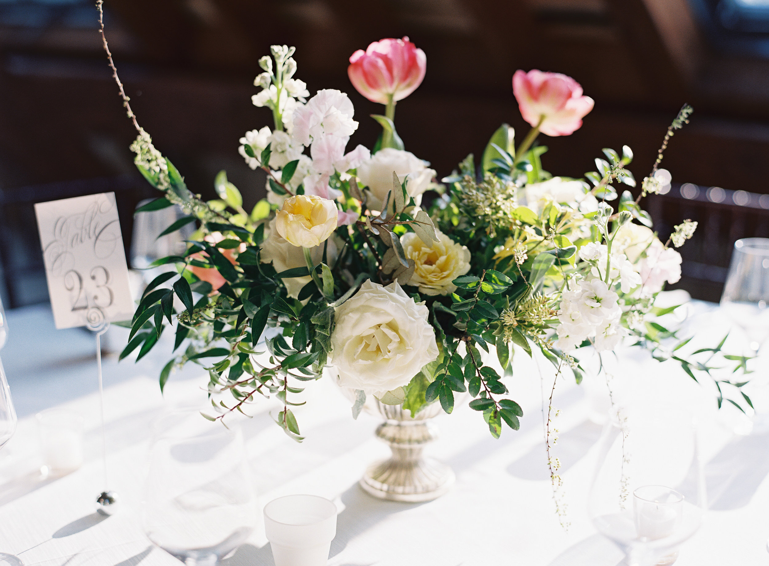 Silver compote centerpieces with natural greenery, peach garden roses, pink tulips, and spirea // Nashville Wedding Floral Design