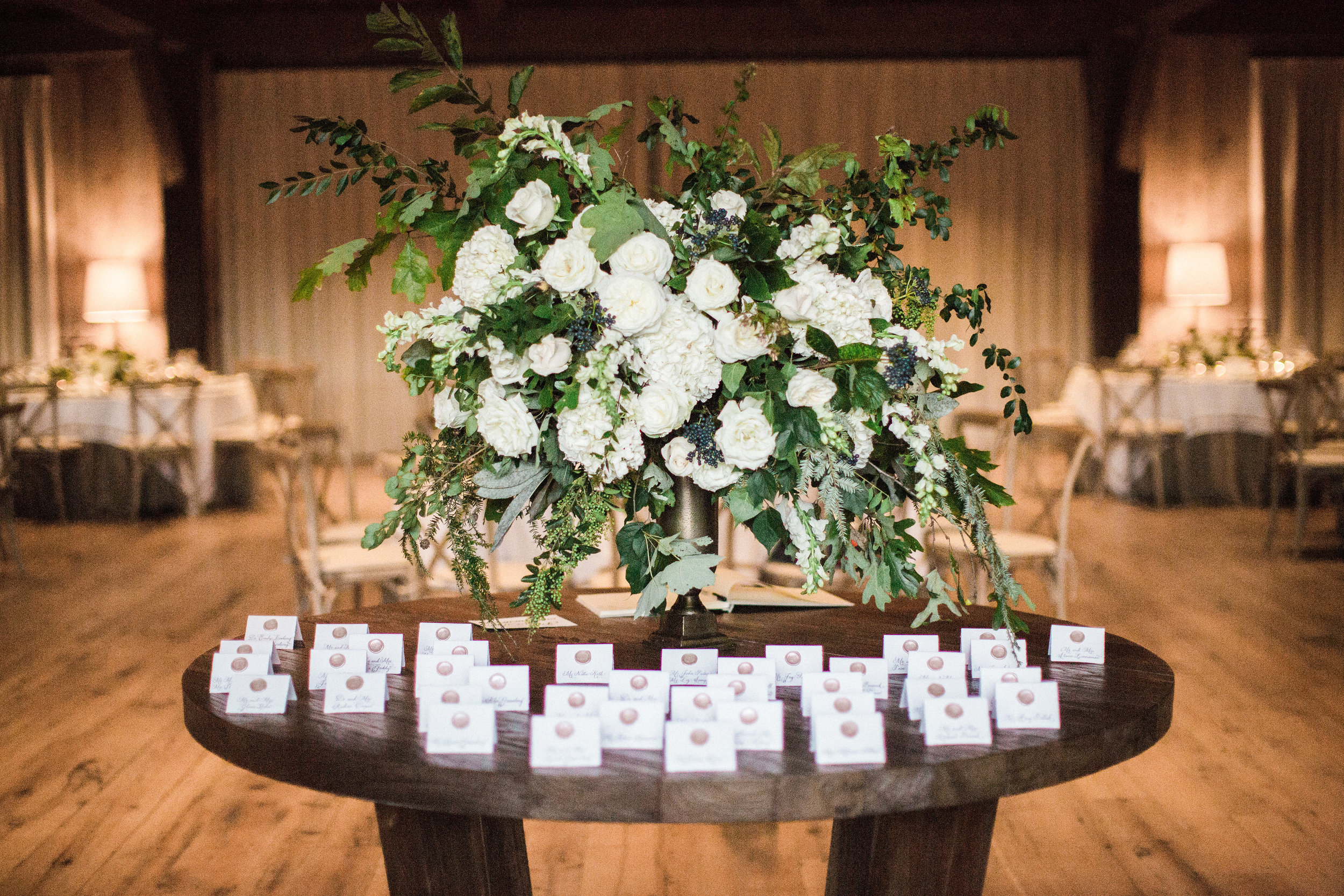 Large, asymmetrical floral arrangement with white flowers and untamed greenery and berries // Blackberry Farm Wedding Floral Design