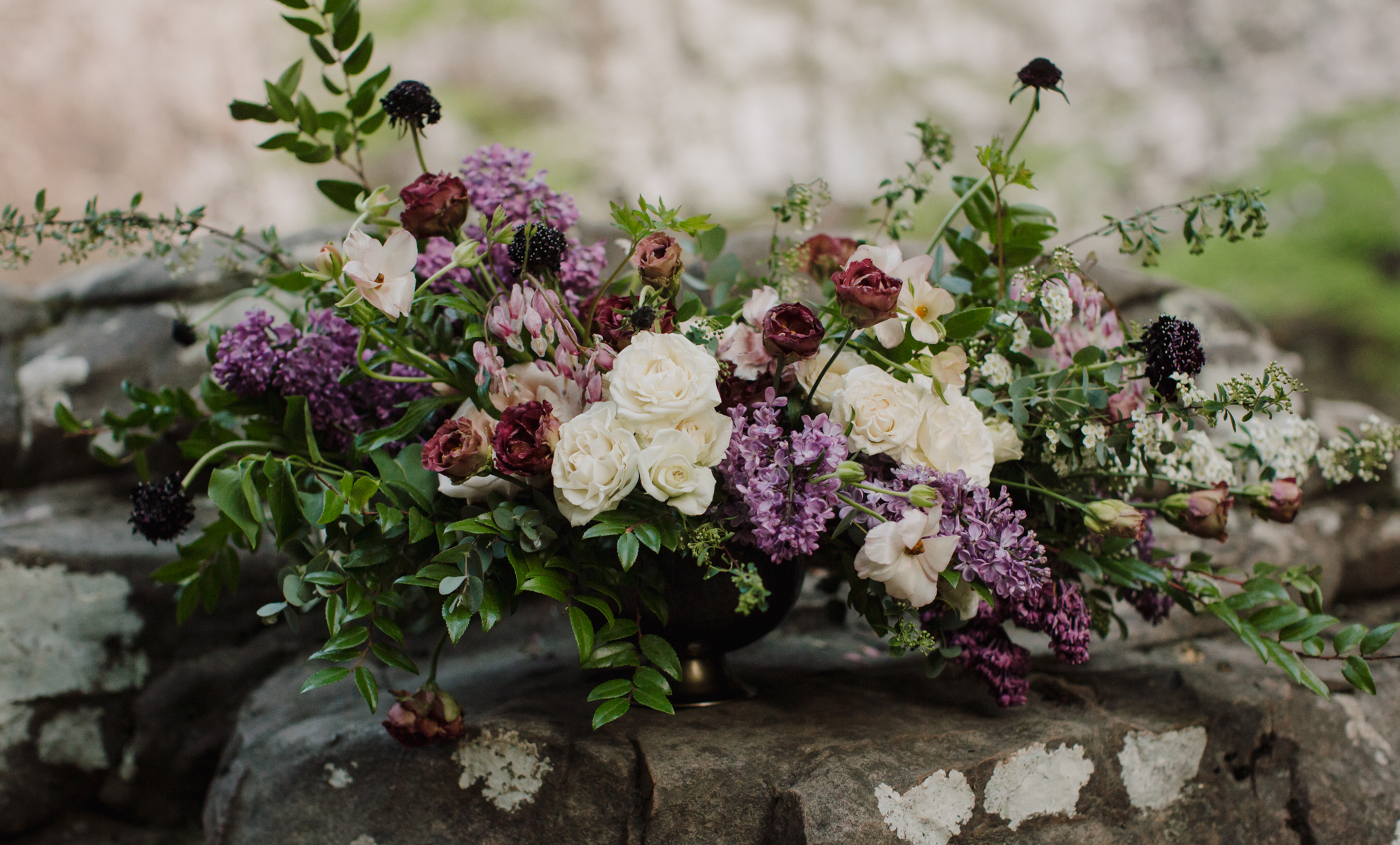 Lush floral centerpiece with lilacs, bleeding hearts, and butterfly ranunculus // Waterfall Vow Renewal in Middle Tennessee