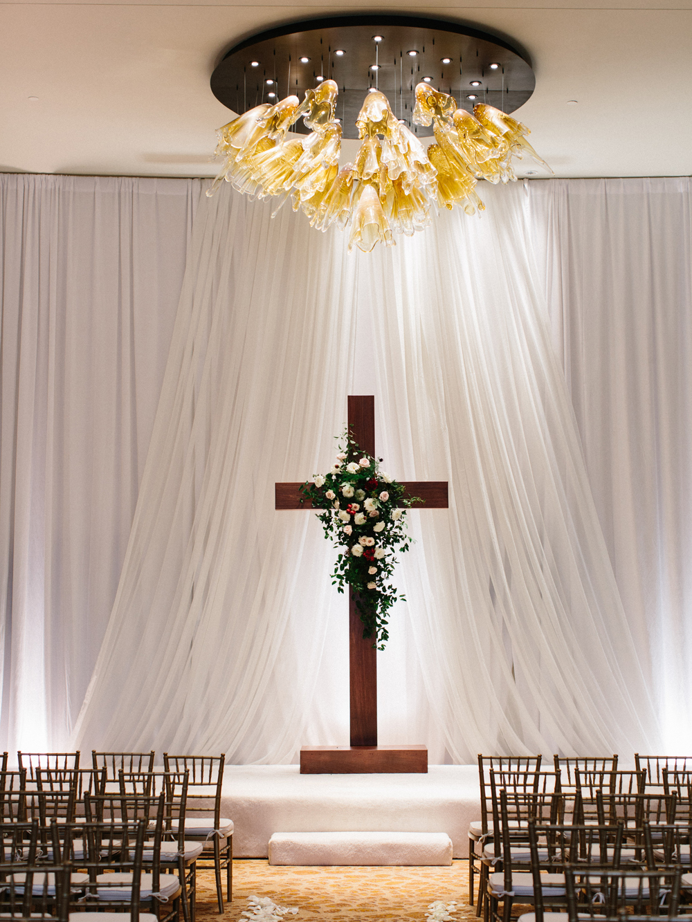 Wooden cross backdrop with lush floral spray // Elegant downtown Nashville wedding flowers