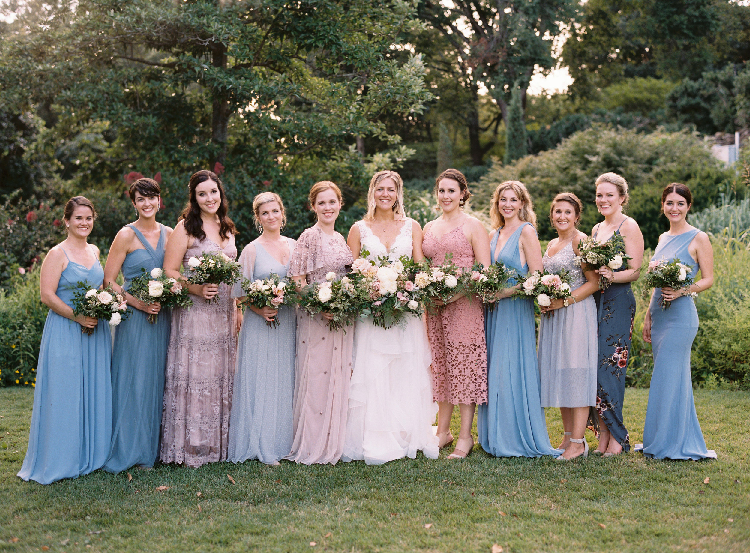 Dusty blue and soft pink bridesmaid dresses with lush, greenery heavy bouquets // Southern US Wedding Floral Design