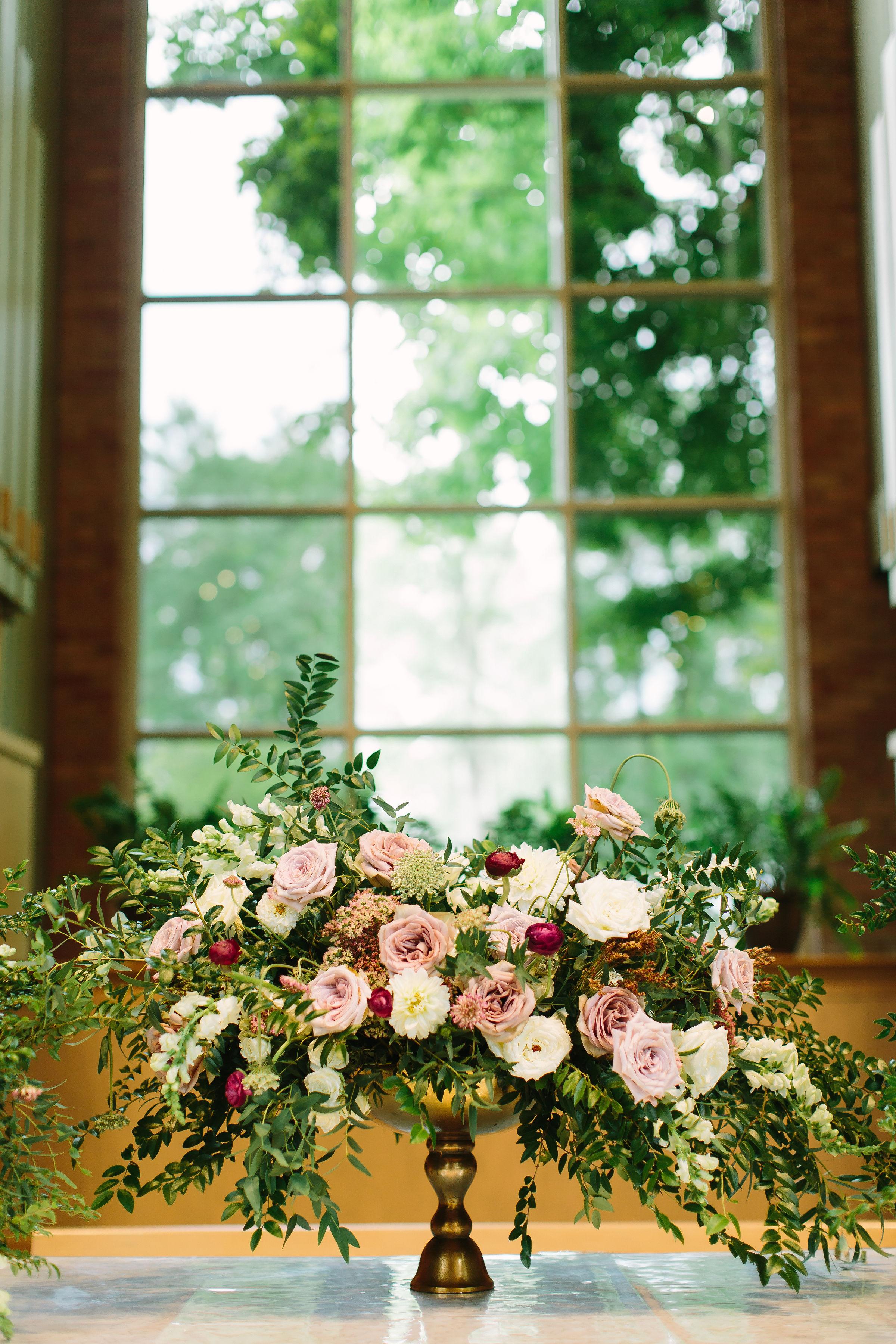 Lush, untamed altar arrangement with hues of dusty mauve, blush, and white // Nashville Wedding Floral Design