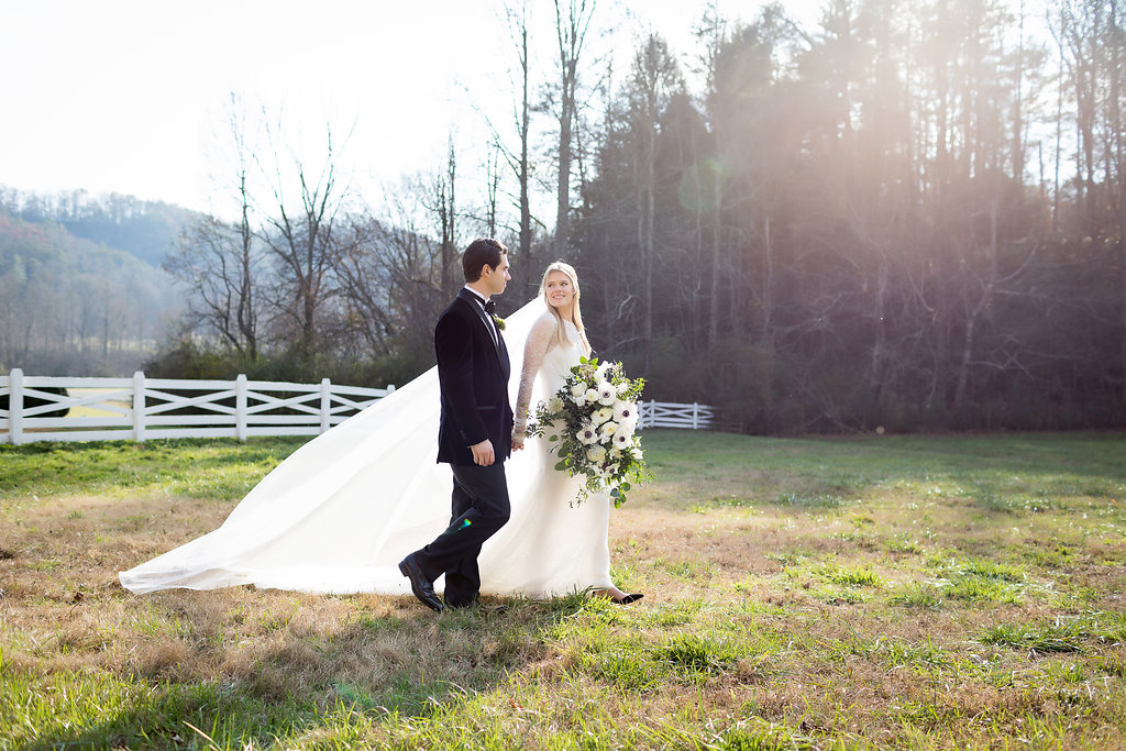 Oversized, asymmetrical bride's bouquet with white flowers and natural, untamed greenery // Tennessee Wedding Floral Design at Blackberry Farm