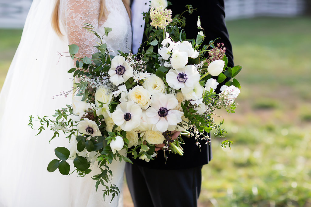 Oversized, asymmetrical bride's bouquet with white flowers and natural, untamed greenery // Southeastern Wedding Floral Design at Blackberry Farm