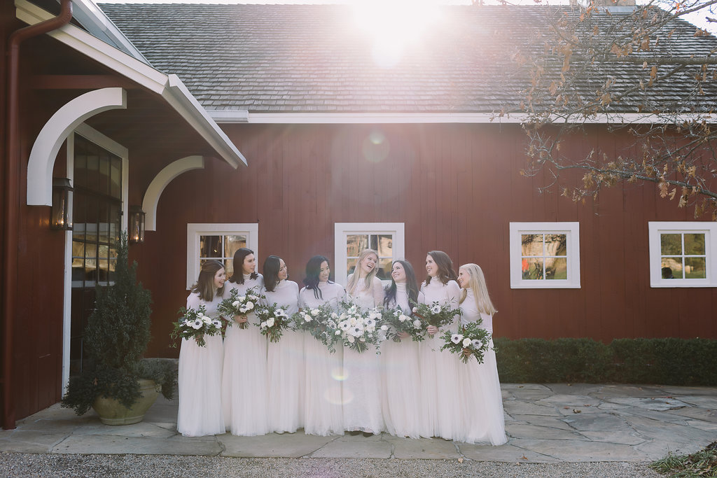 All white bridesmaid style with cashmere turtlenecks, tulle skirts, and loose bouquets of white florals and natural greenery // Nashville Wedding Flowers