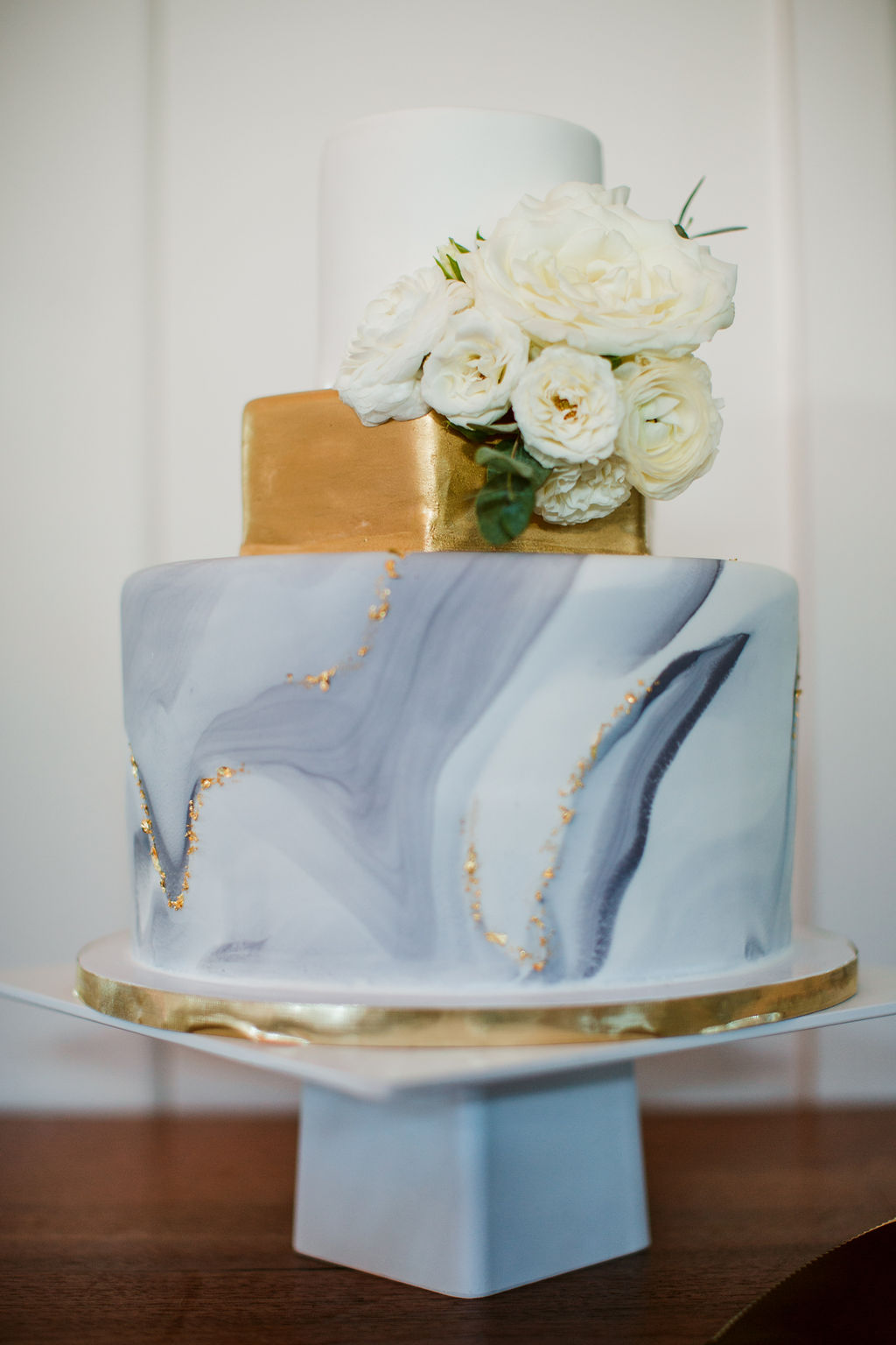 Marbled cake with all white flowers and touches of greenery