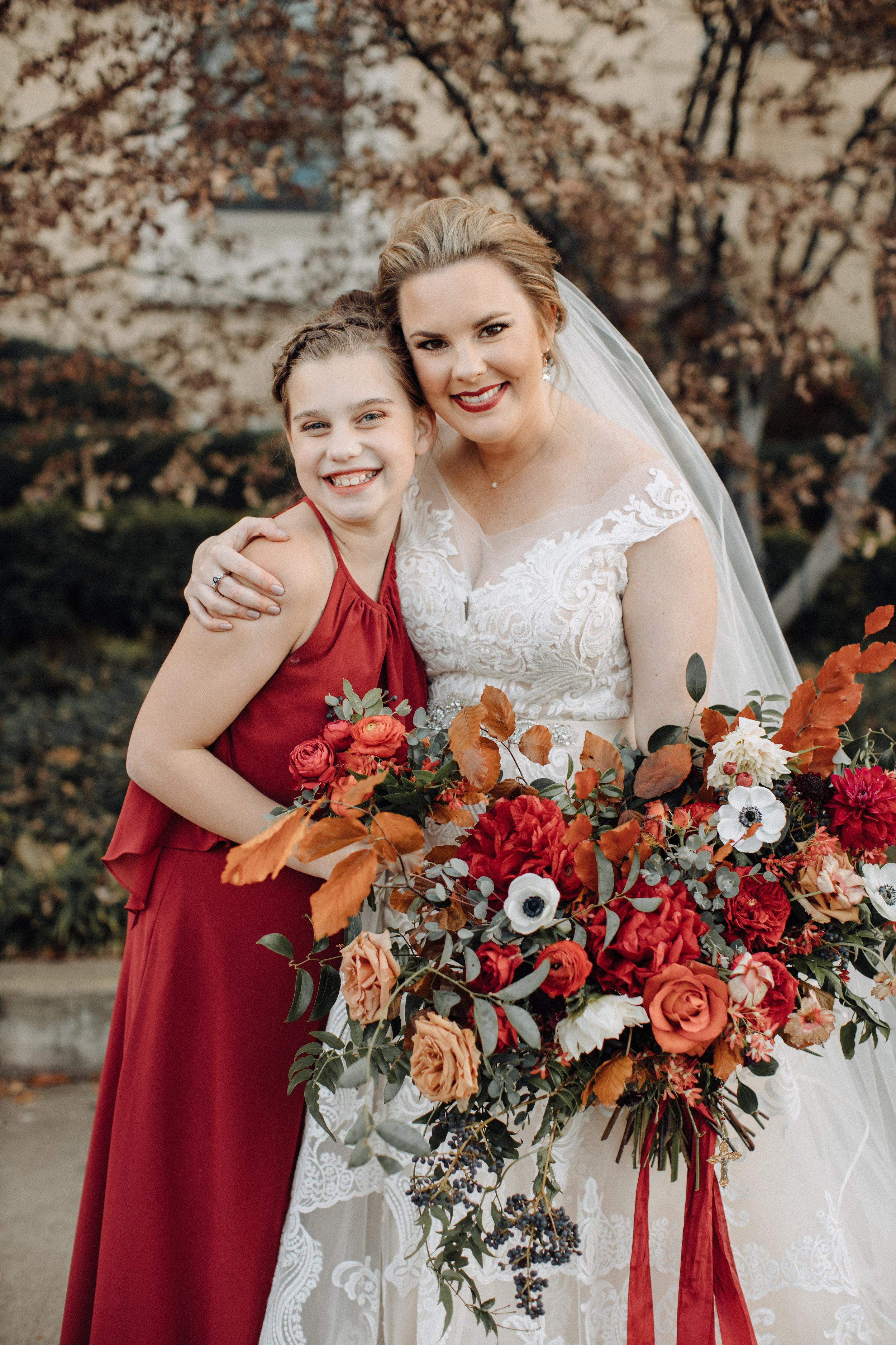 Burgundy velvet bridesmaid dresses with lush, asymmetrical bouquets using garden roses, ranunculus, and anemones