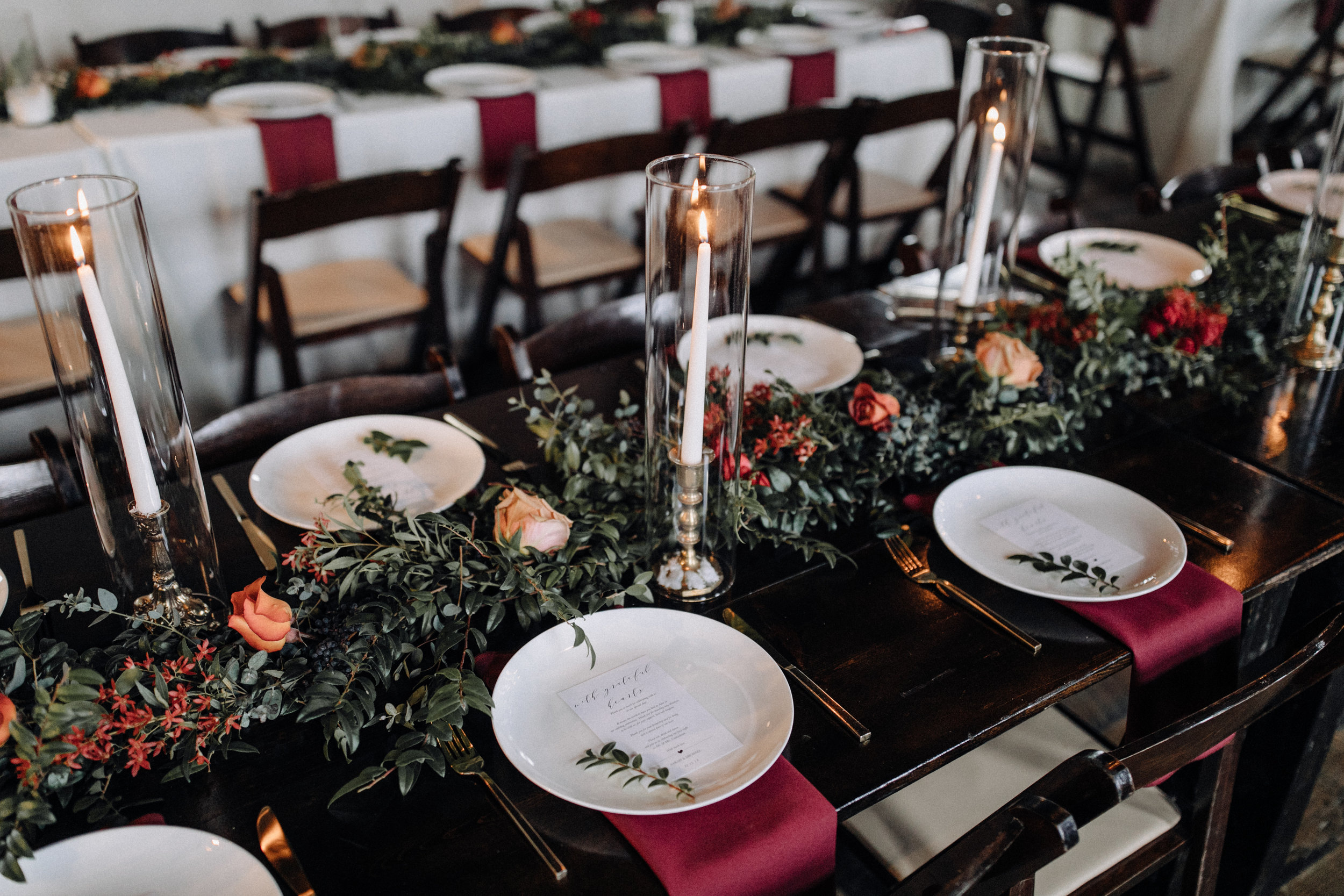 Garland table runner of eucalyptus and natural greenery with copper and burgundy floral accents. Garden-inspired wedding florals at the Cordelle, Nashville.