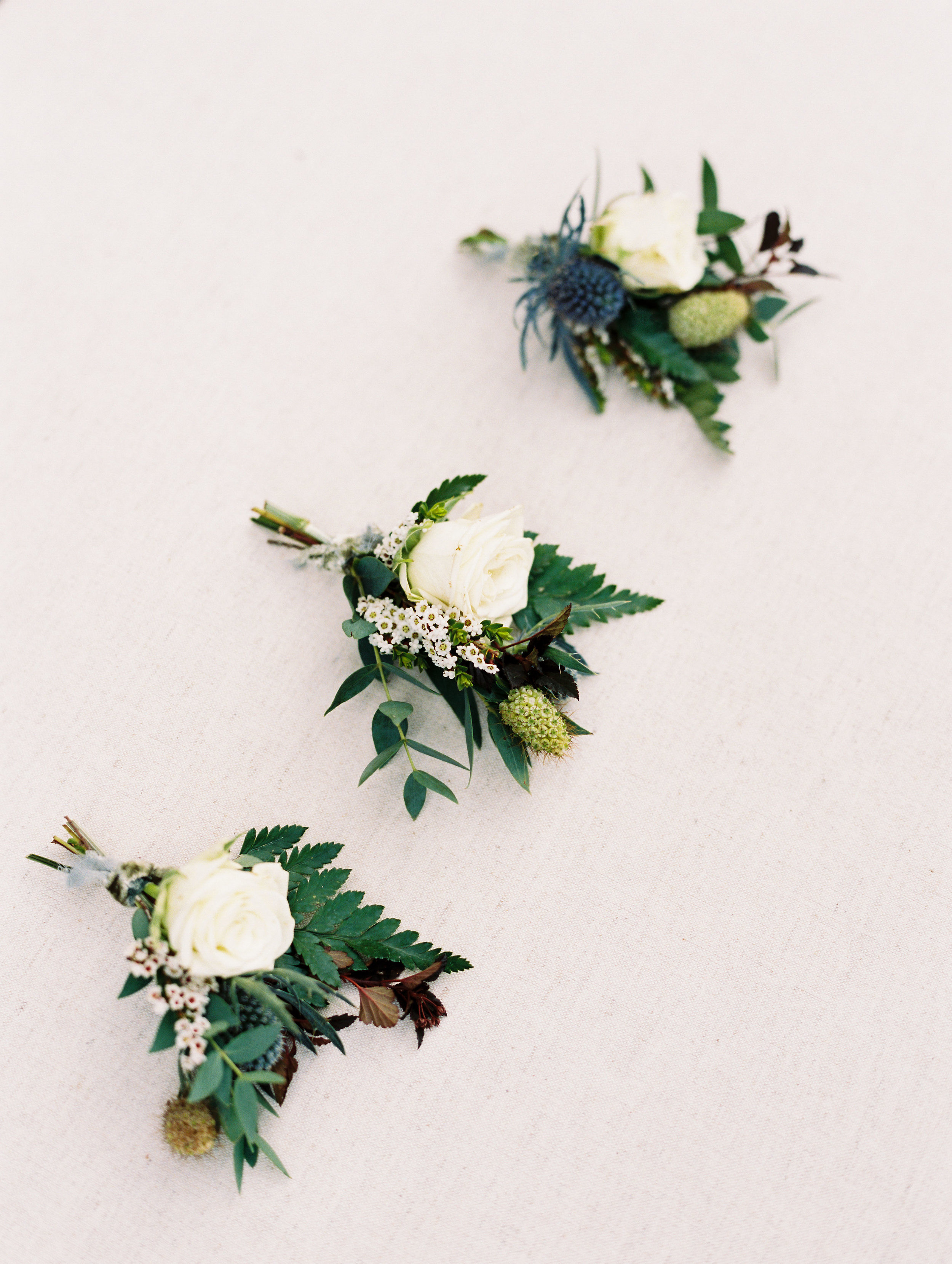Texture boutonnieres with blue thistles and greenery. Destination Wedding Floral Design