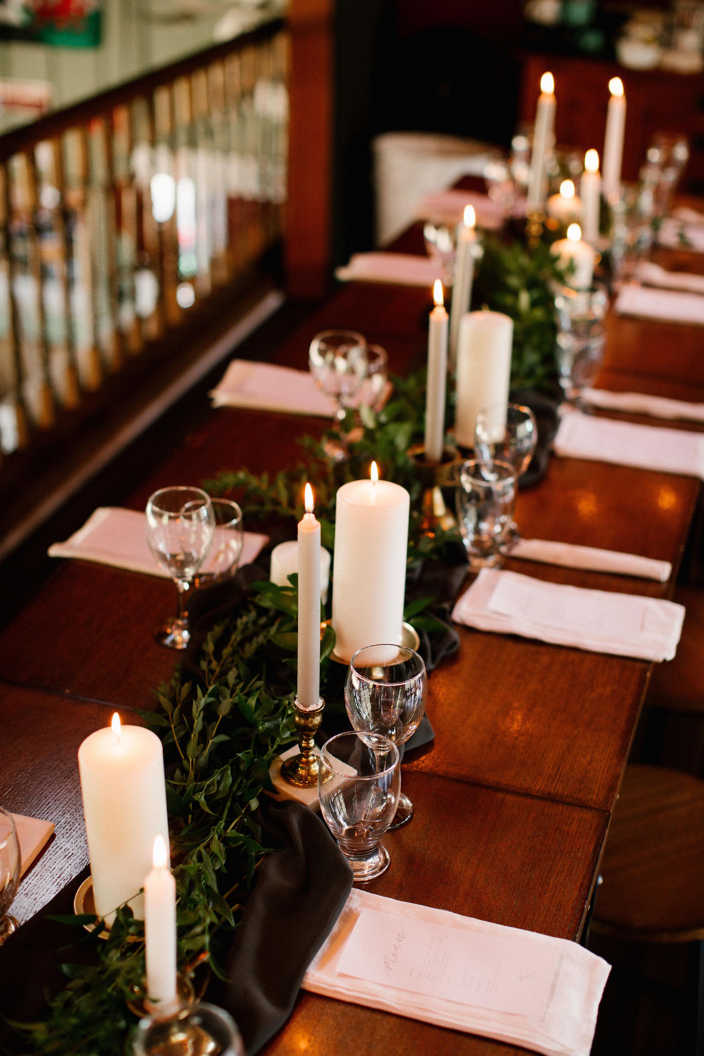 Lush greenery runner with brass candlesticks. Destination Wedding Floral Design.