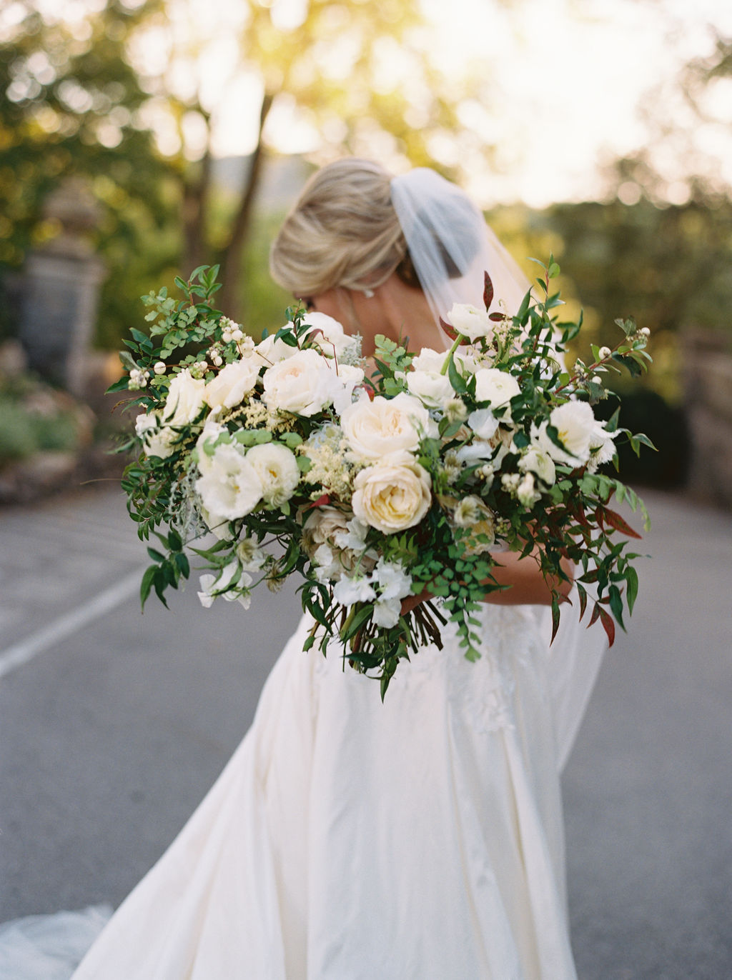 Untamed, asymmetrical bride's bouquet with all white flowers and natural greenery. Southeast US Wedding Floral Design.