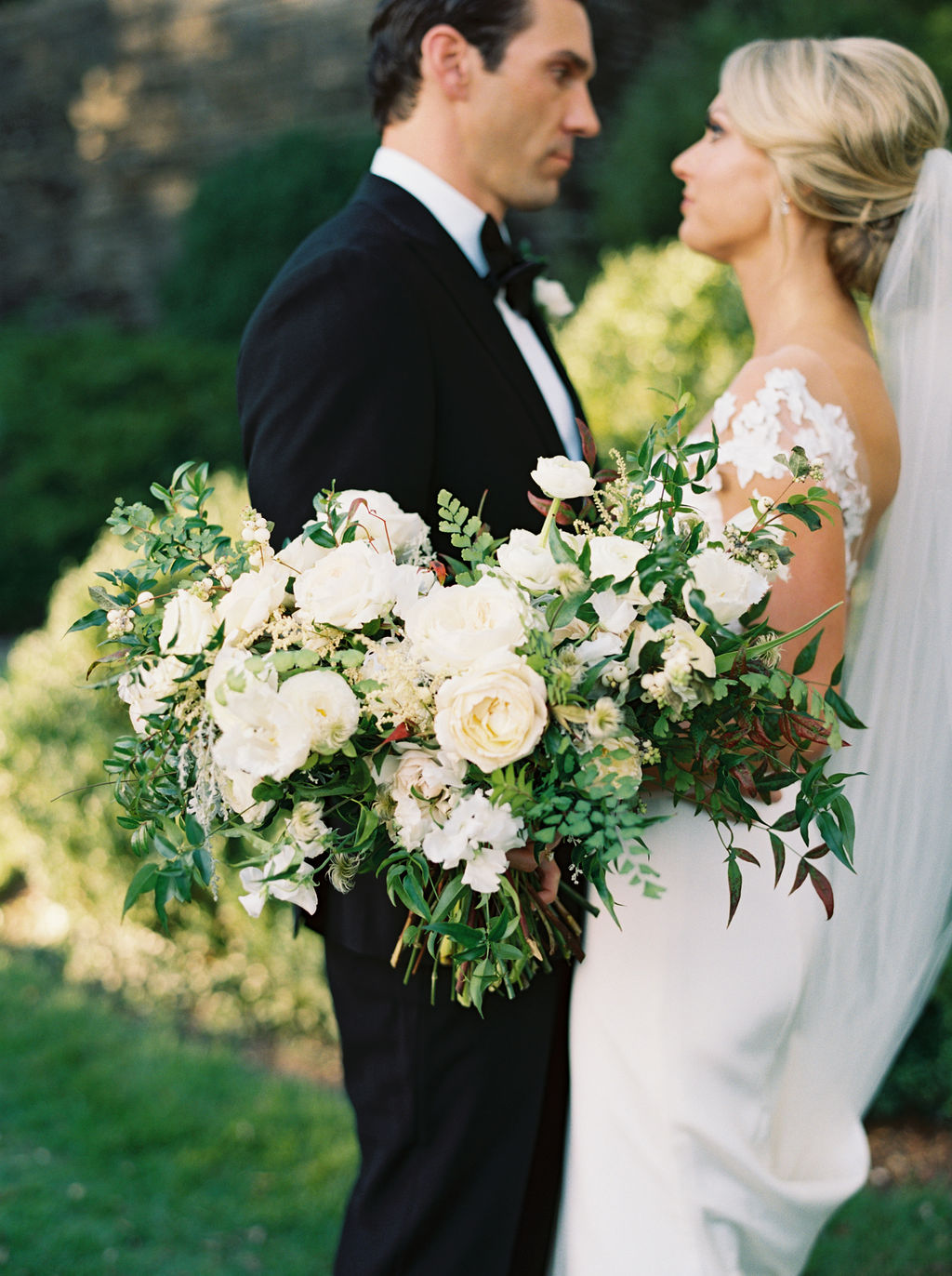 Natural, organic bridal bouquet with white garden roses, ranunculus, and lush greenery. Nashville, TN Wedding Florist.