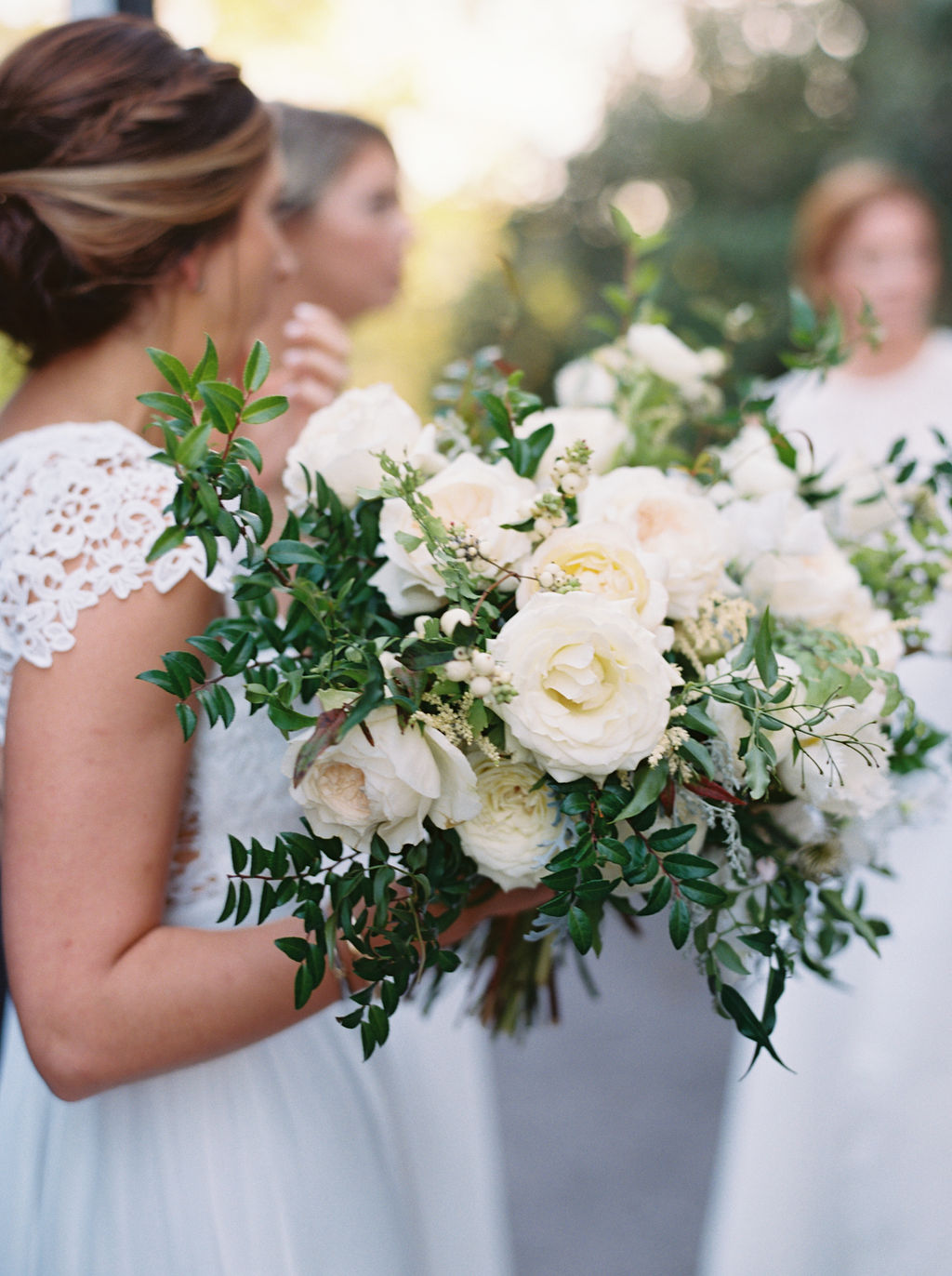 All white bridesmaid dresses with white flowers and greenery. Nashville Wedding Floral Design.