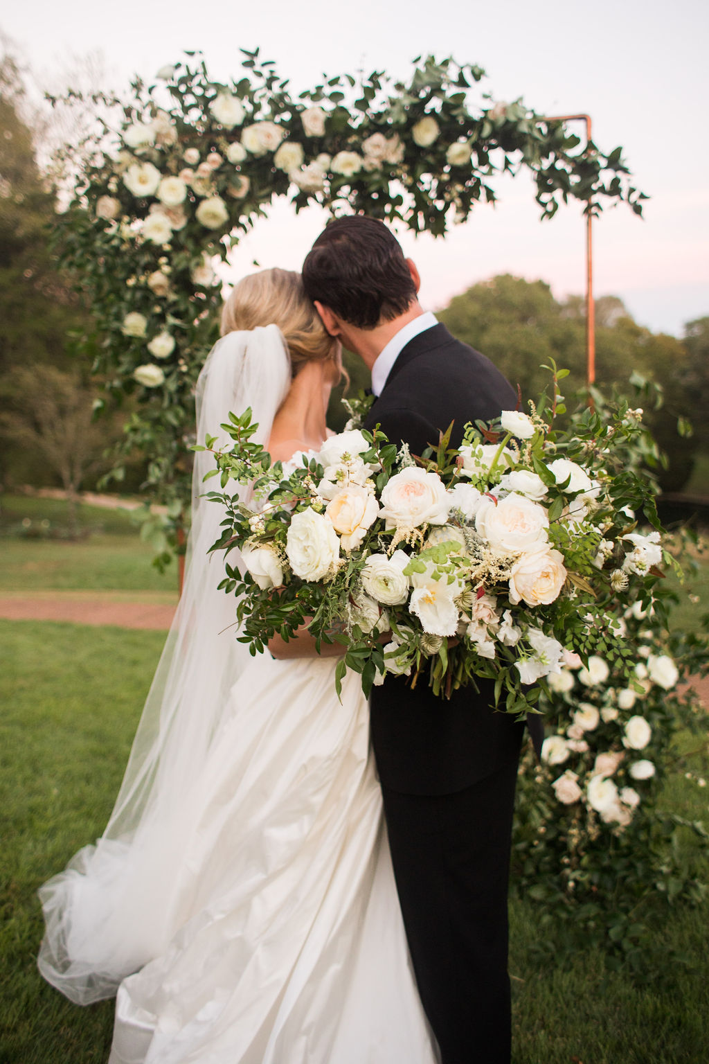 Modern copper arch with lush, garden-inspired florals and greenery. Cheekwood Wedding Flowers.