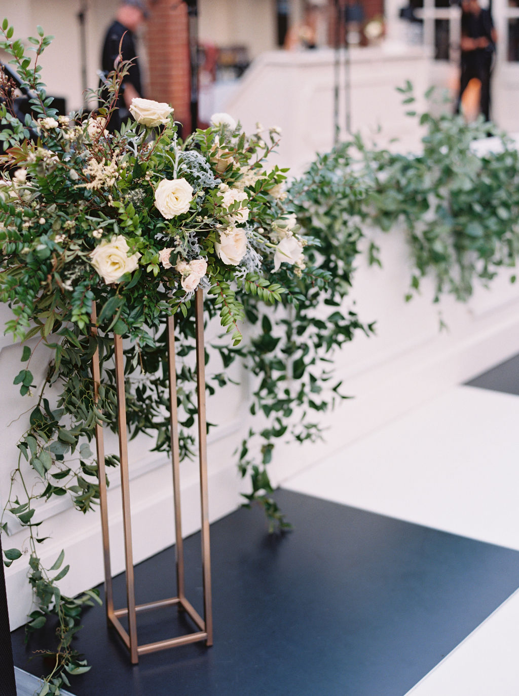 Modern gold stands overflowing with natural greenery and white floral centerpieces. Southeast US Wedding Floral Designer
