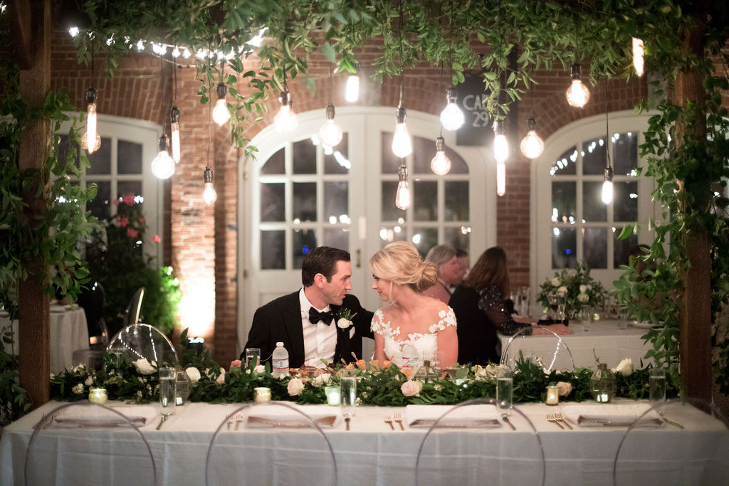 Wooden garden trellis over the head table with natural, vine-like greenery and floral garlands. Nashville Wedding Florist.