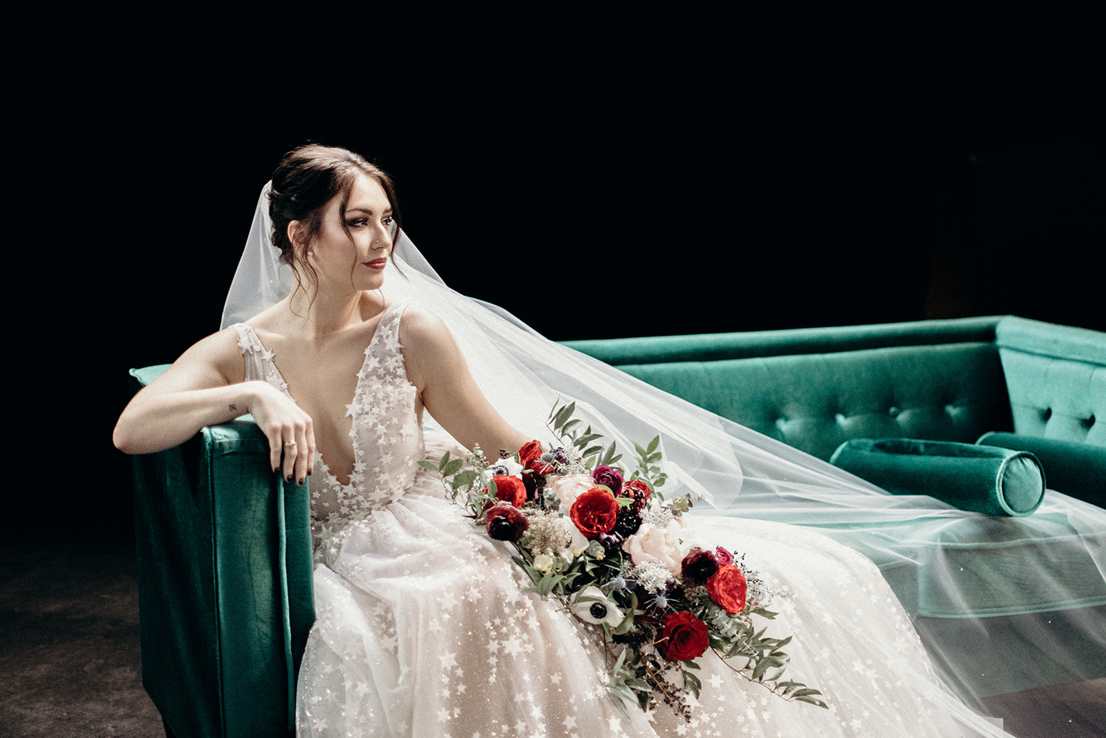 Starry wedding dress with an untamed, airy bridal bouquet with garden roses, ranunculus, and anemones in hues of burgundy and jewel tones. Bonus: green velvet couch! Wedding Floral Designer in Nashville, TN.