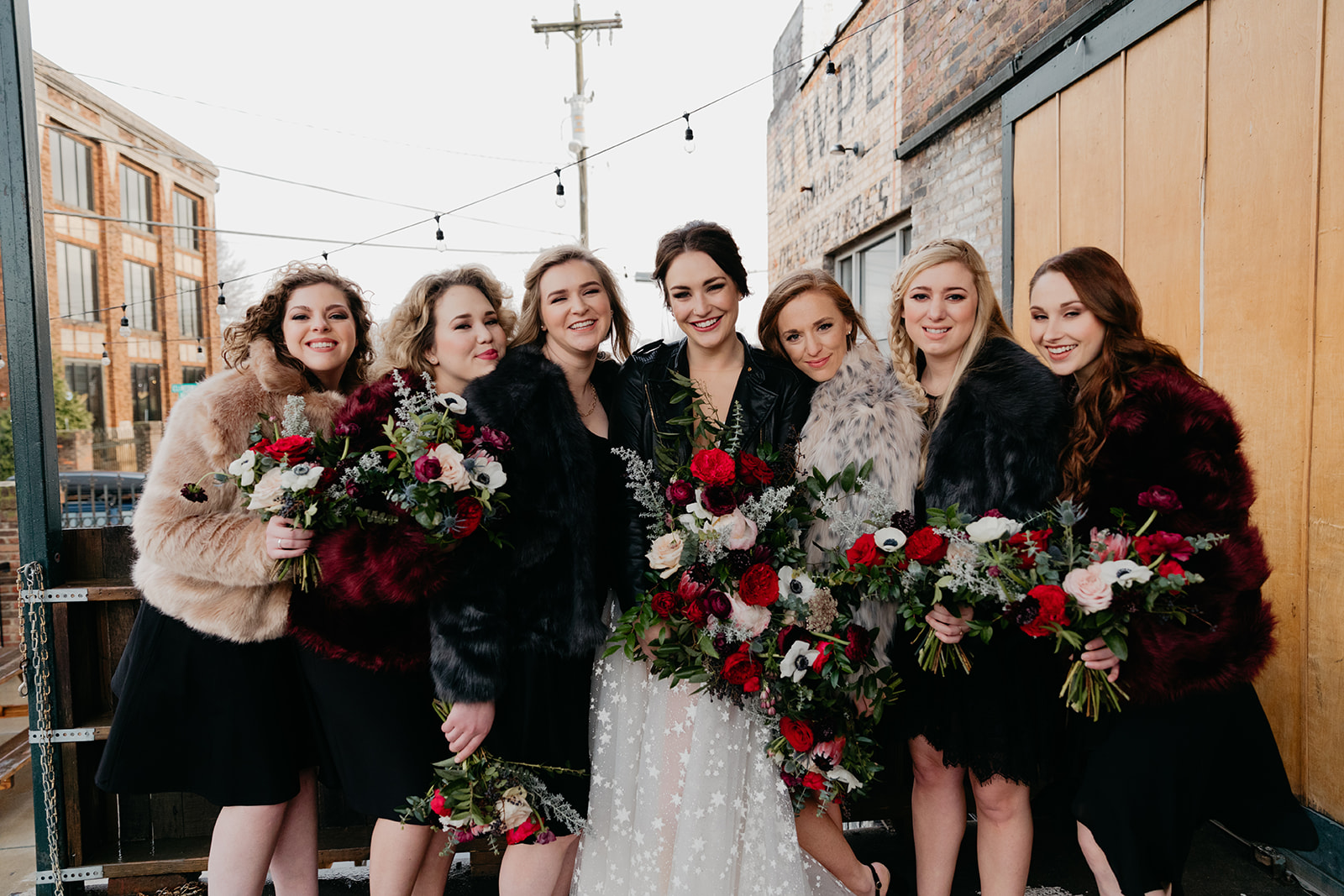 Burgundy, eggplant, and blush bouquets with black bridesmaid dresses and the bride in a leather jacket! Badass Nashville wedding florals.