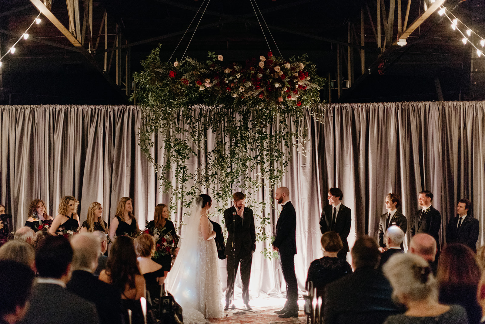 Candlelit entrance for the bride with a hanging floral installation for the wedding ceremony backdrop! Nashville Wedding flowers at Marathon Music Works.