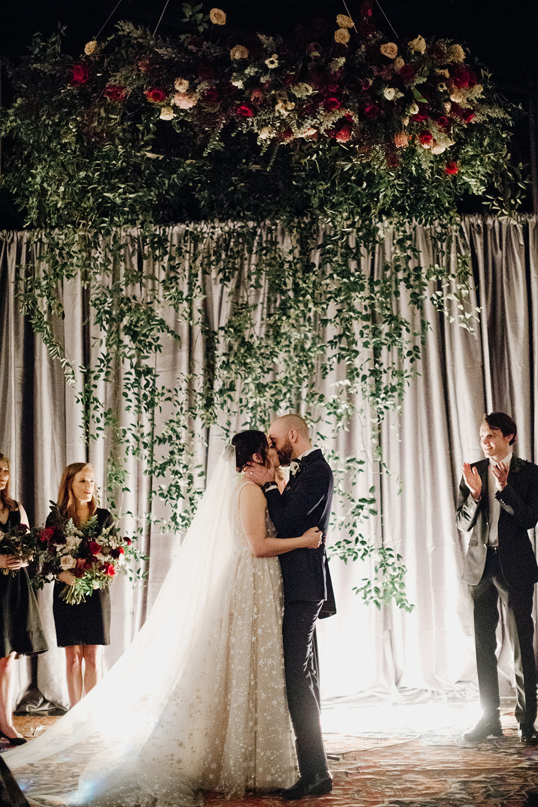 Oversized wreath floral installation with eggplant and burgundy florals and a curtain of greenery. Nashville Wedding Floral Design.