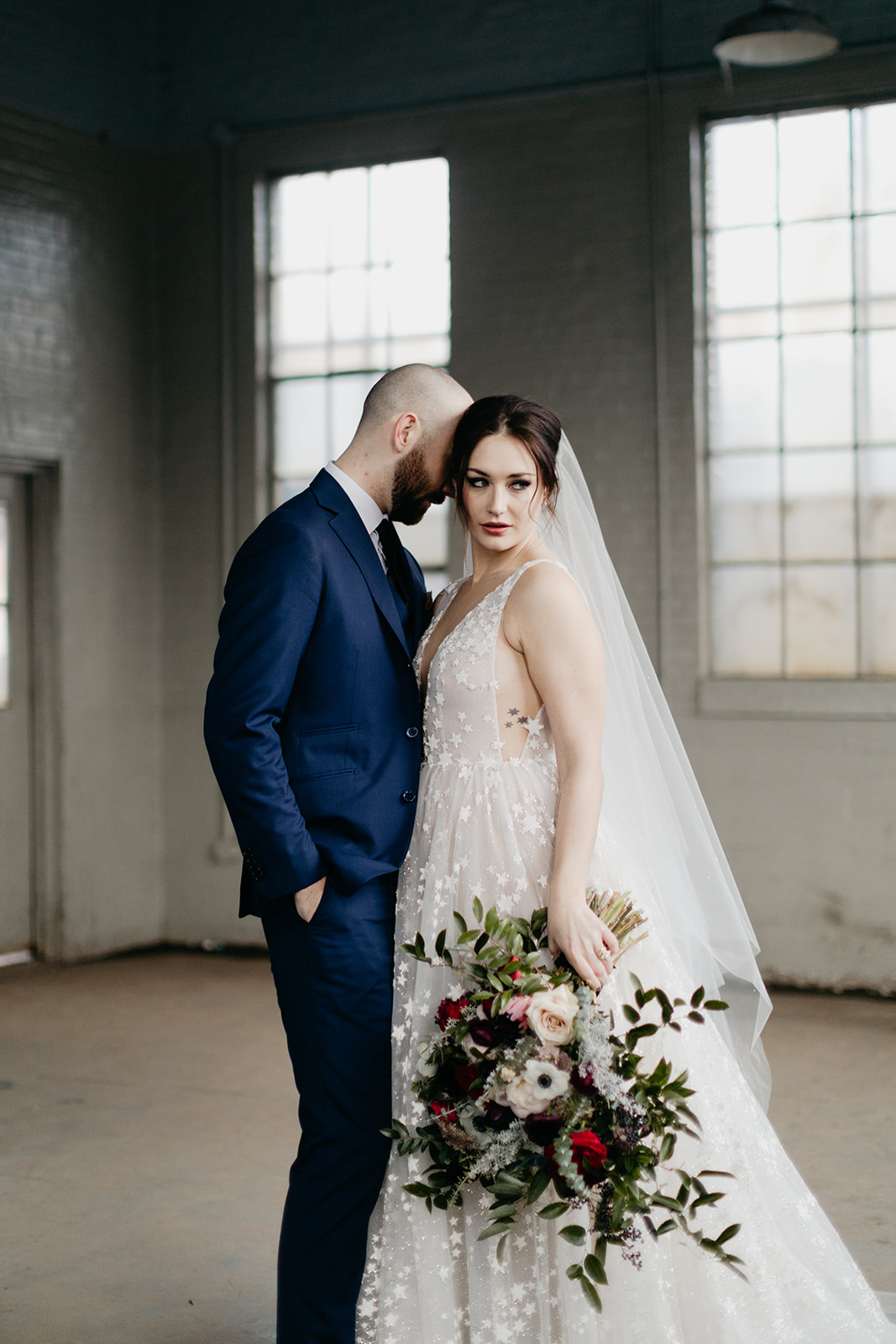 Starry wedding dress with an untamed, airy bridal bouquet with garden roses, ranunculus, and anemones in hues of burgundy and jewel tones. Wedding Floral Designer in Nashville, TN.