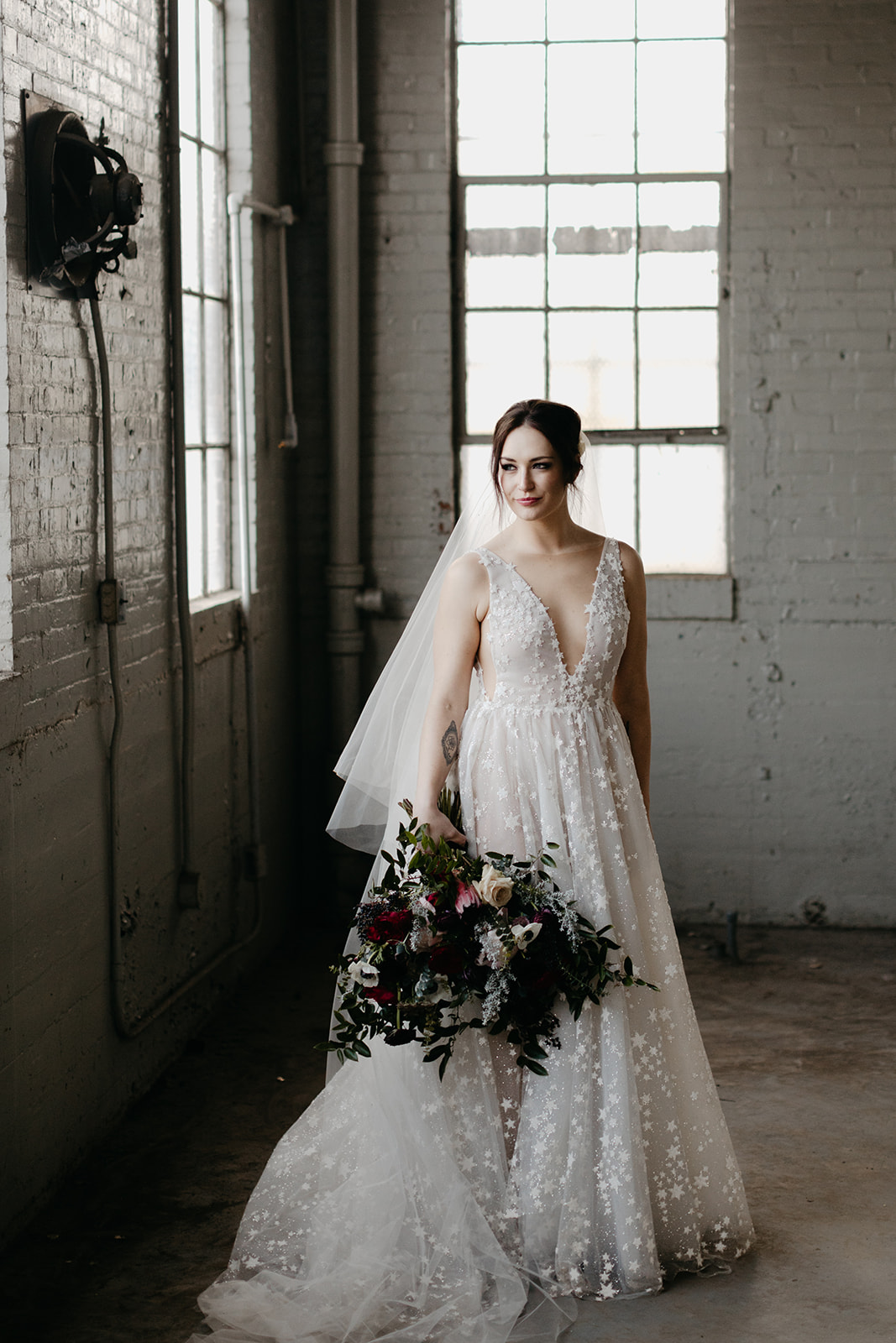 Starry wedding dress with an untamed, airy bridal bouquet with garden roses, ranunculus, and anemones in hues of burgundy and jewel tones.