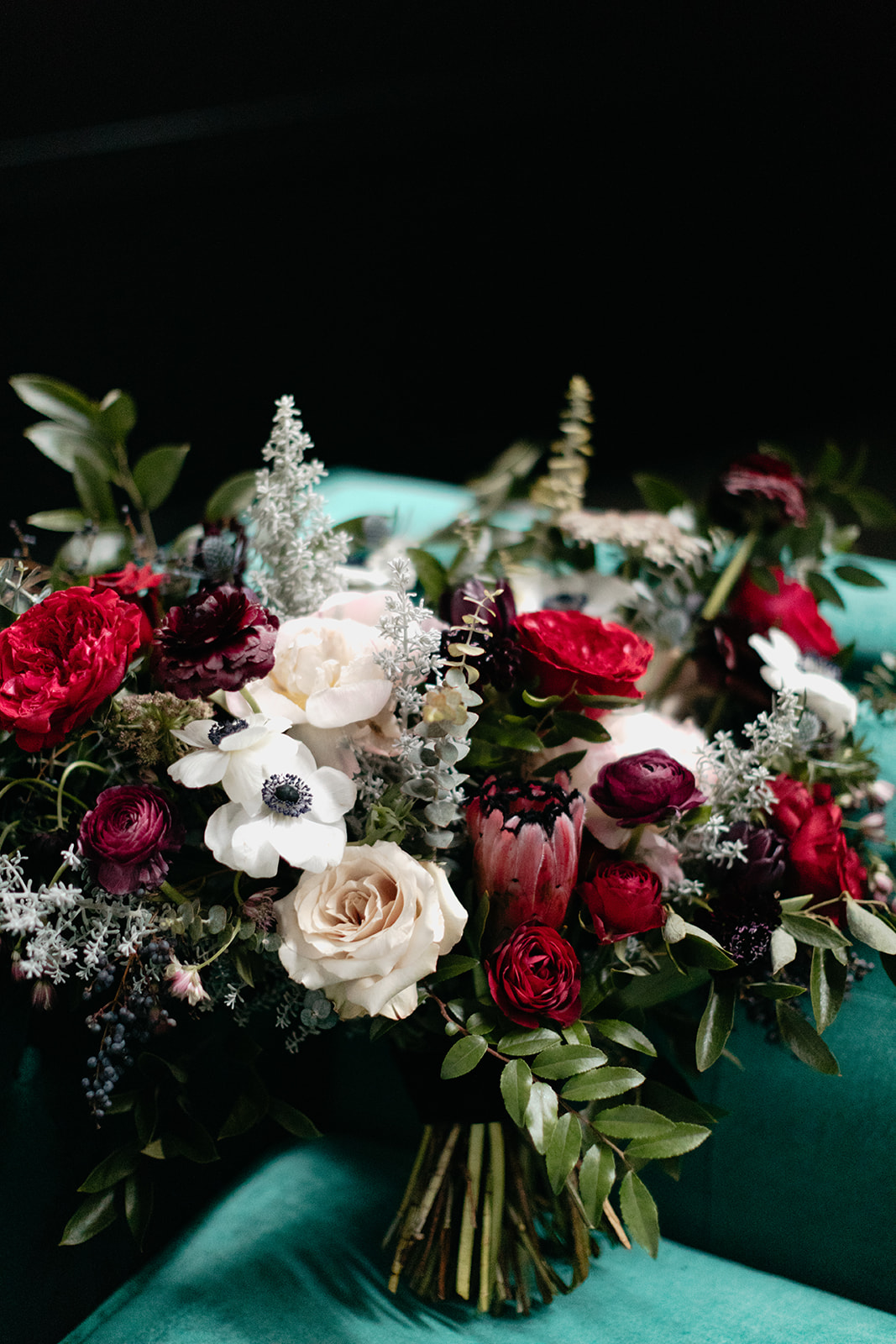 Lush, wintry bridal bouquet with garden roses, anemones, ranunculus, and greenery. Nashville Wedding Florist.