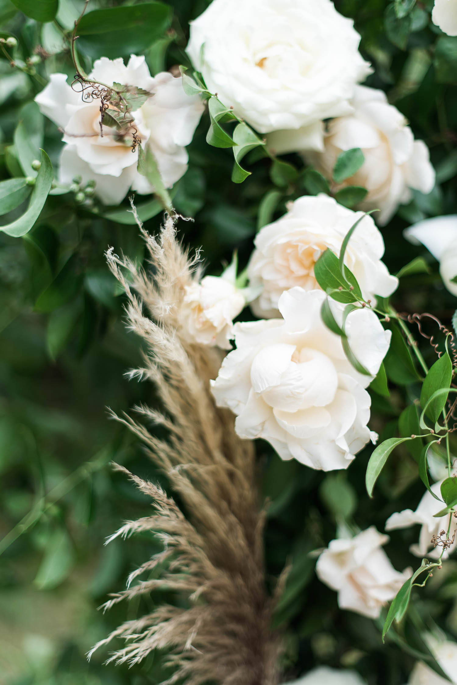 Lush wedding arch with untamed greenery, garden roses, textures, and antlers. Nashville Wedding Florist.