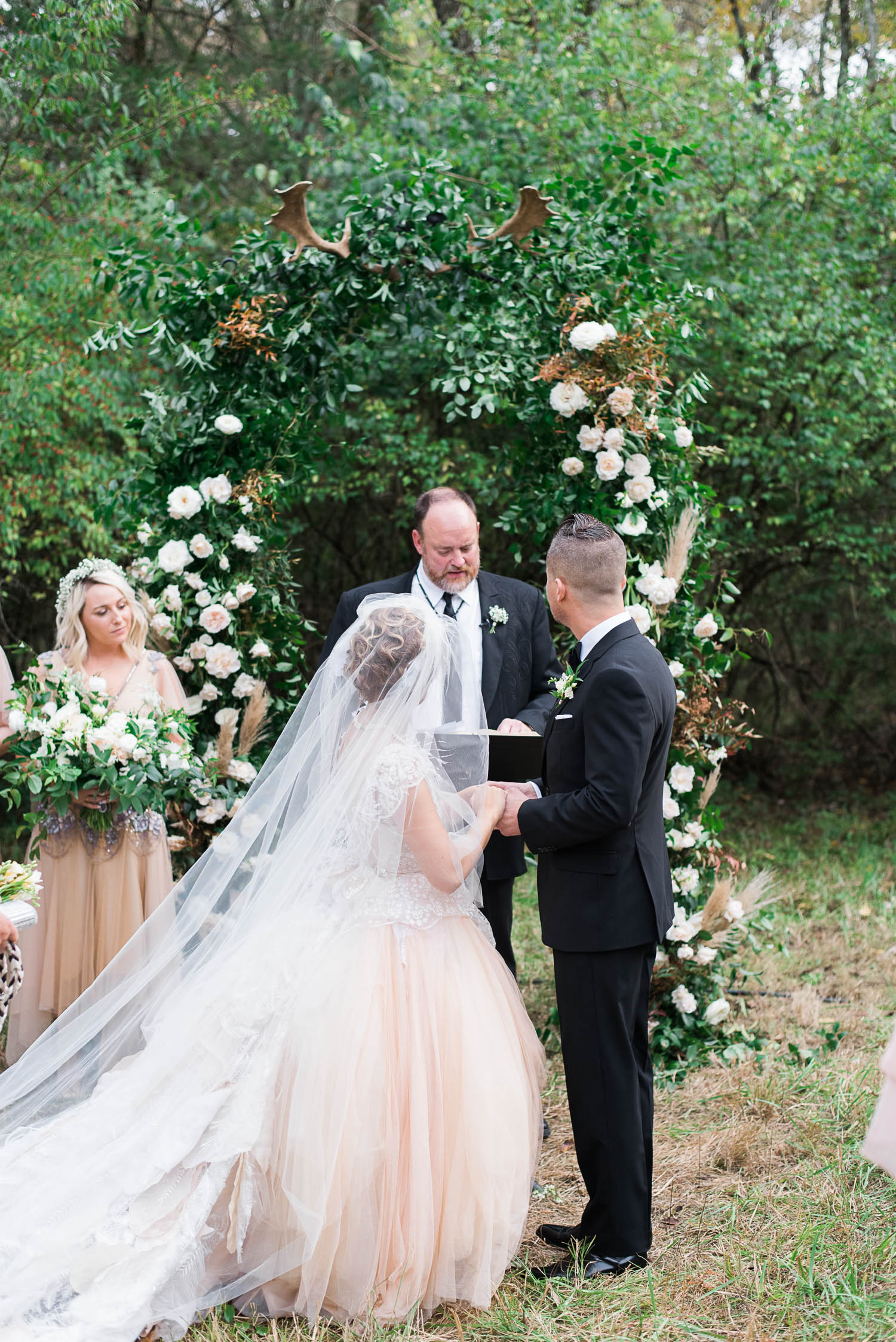 Lush wedding arch with greenery, garden roses, and antlers. Nashville Wedding Floral Design.