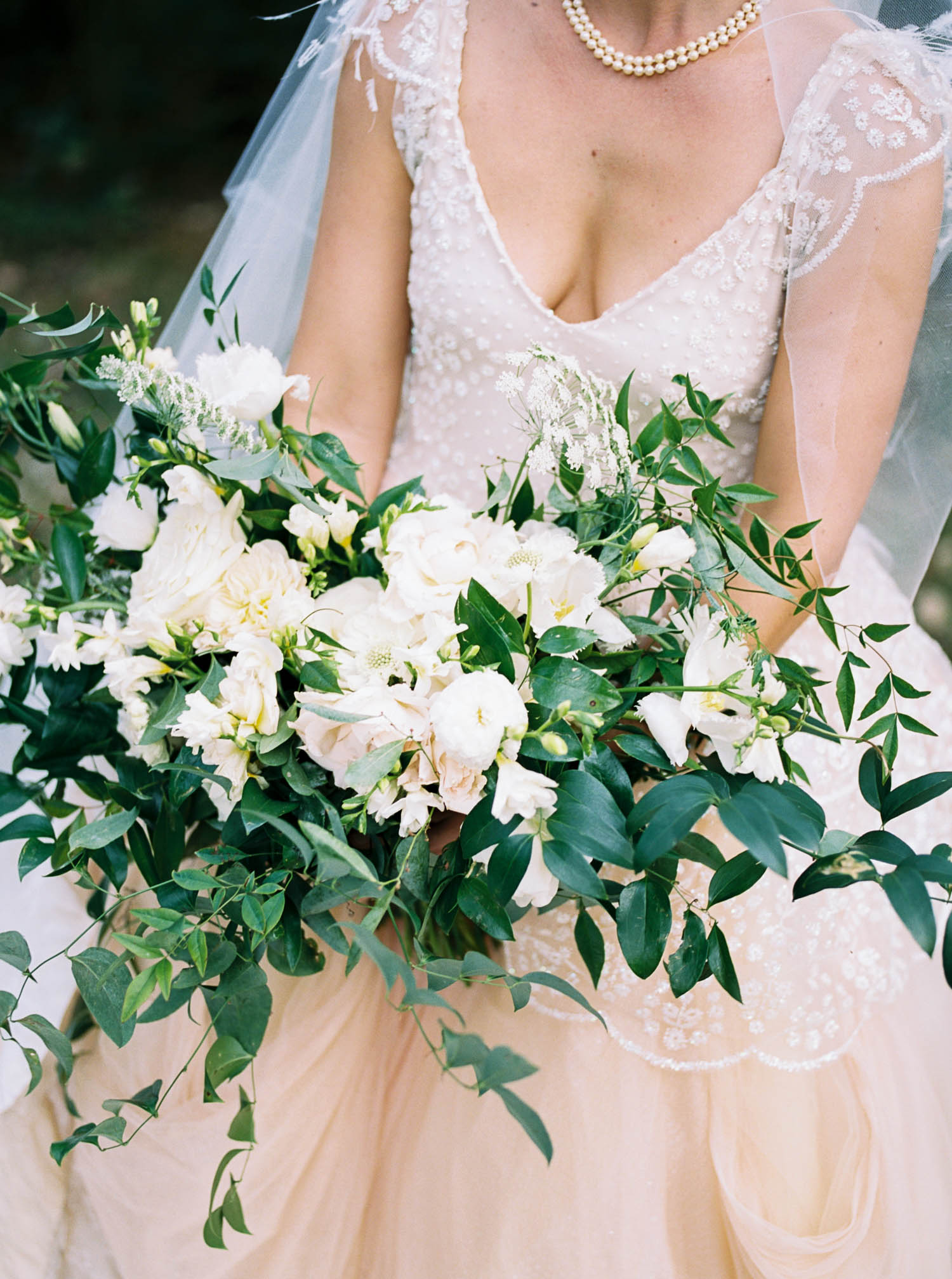 Garden-inspired bridal bouquet with garden roses, ranunculus, and lush, trailing greenery. Nashville Wedding Floral Design.