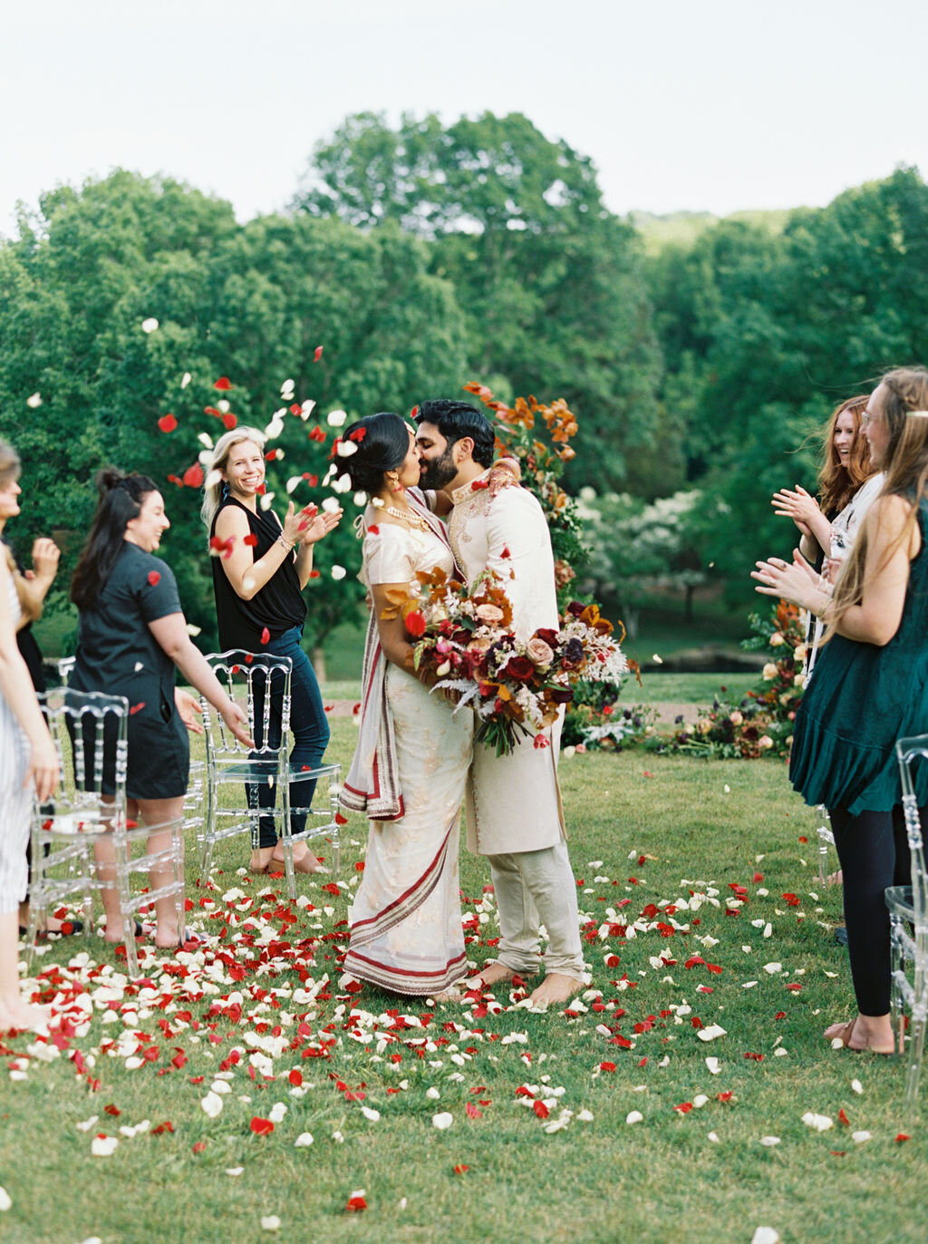 Freestanding wedding ceremony backdrop with lush greenery and bright flowers. Rose petal toss at the end of the wedding ceremony.Nashville wedding floral design by Rosemary & Finch.