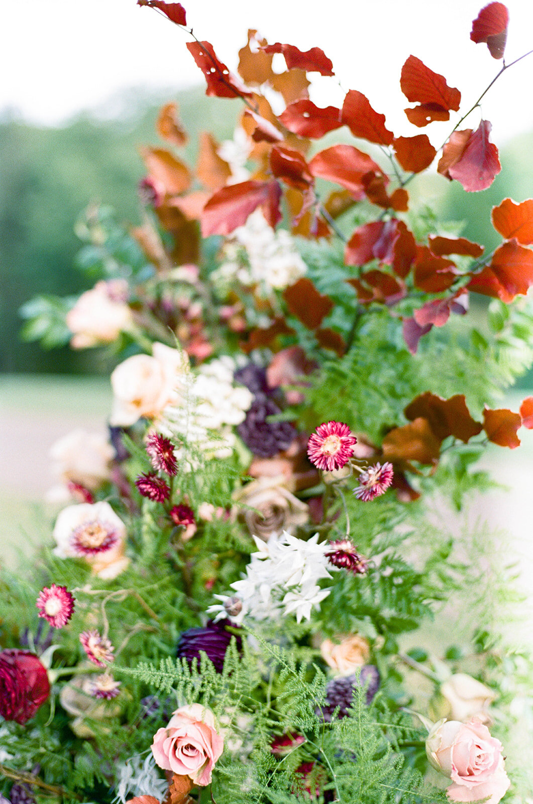Freestanding wedding ceremony backdrop with lush greenery and a bright flowers. Nashville wedding floral design by Rosemary & Finch.