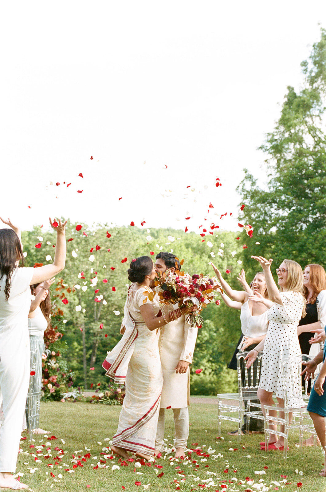 Freestanding wedding ceremony backdrop with lush greenery and a bright flowers. Petal toss at the end of the wedding ceremony. Nashville wedding floral design by Rosemary & Finch.