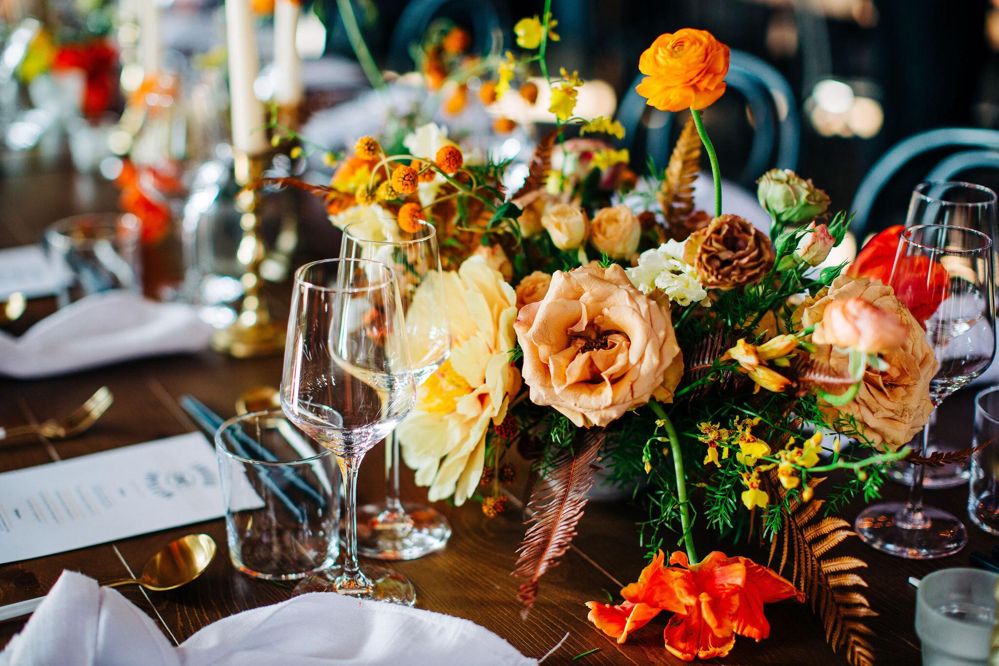 Yellow peonies, orange ranunculus, and golden fern floral centerpieces. Nashville wedding florist.