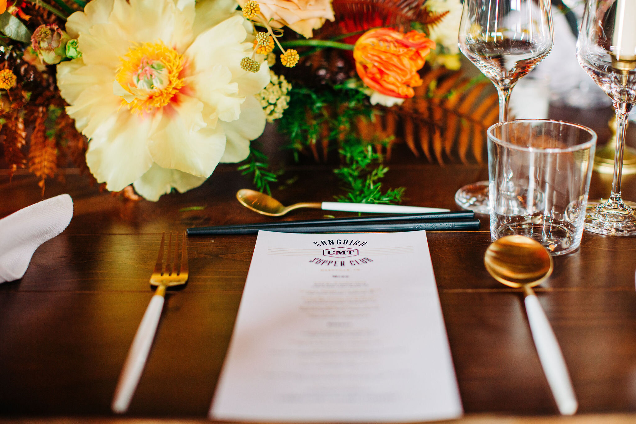 Yellow peonies, orange ranunculus, and golden fern floral centerpieces with brass candlesticks. Nashville wedding florist.